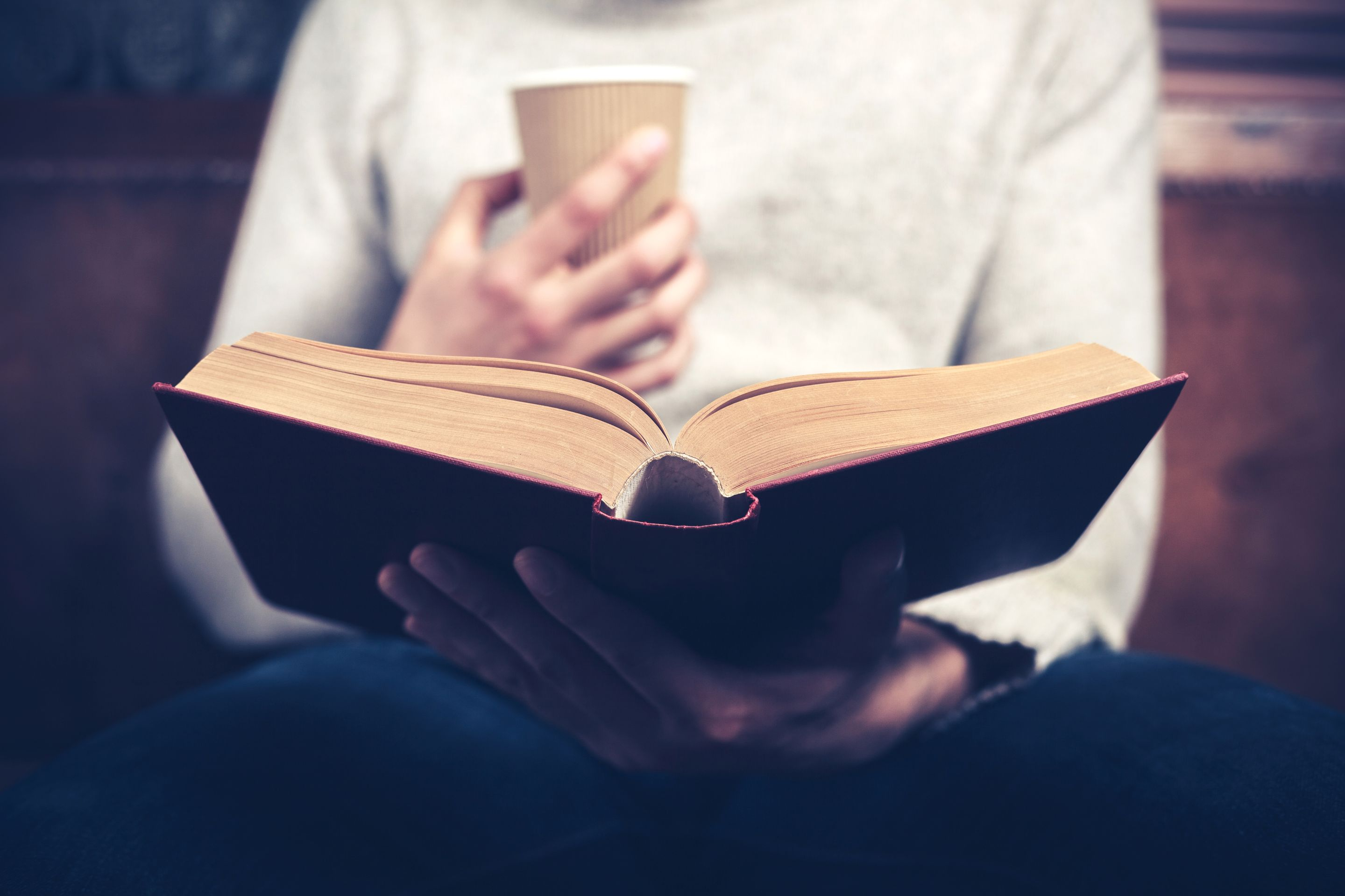 A man reading a book with a cup of coffee in his hand