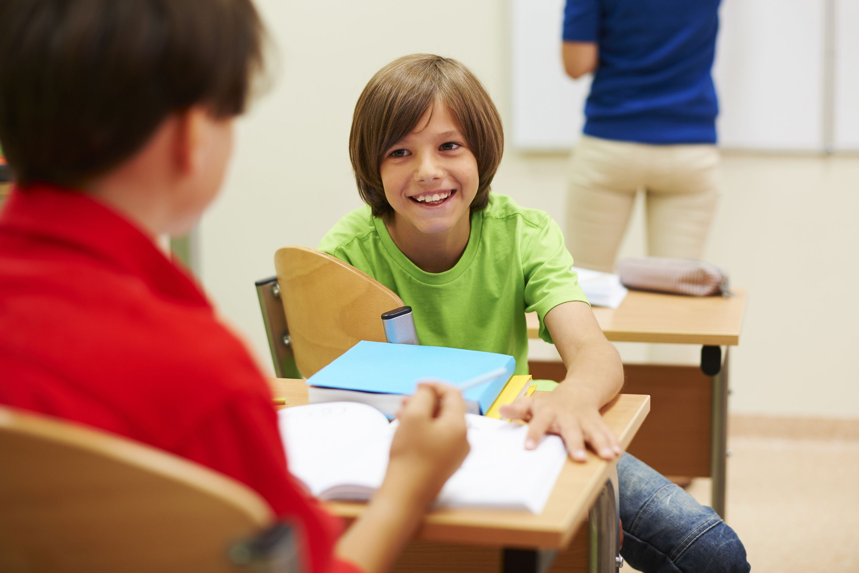 Two young boys smiling and talking with each other in a classroom