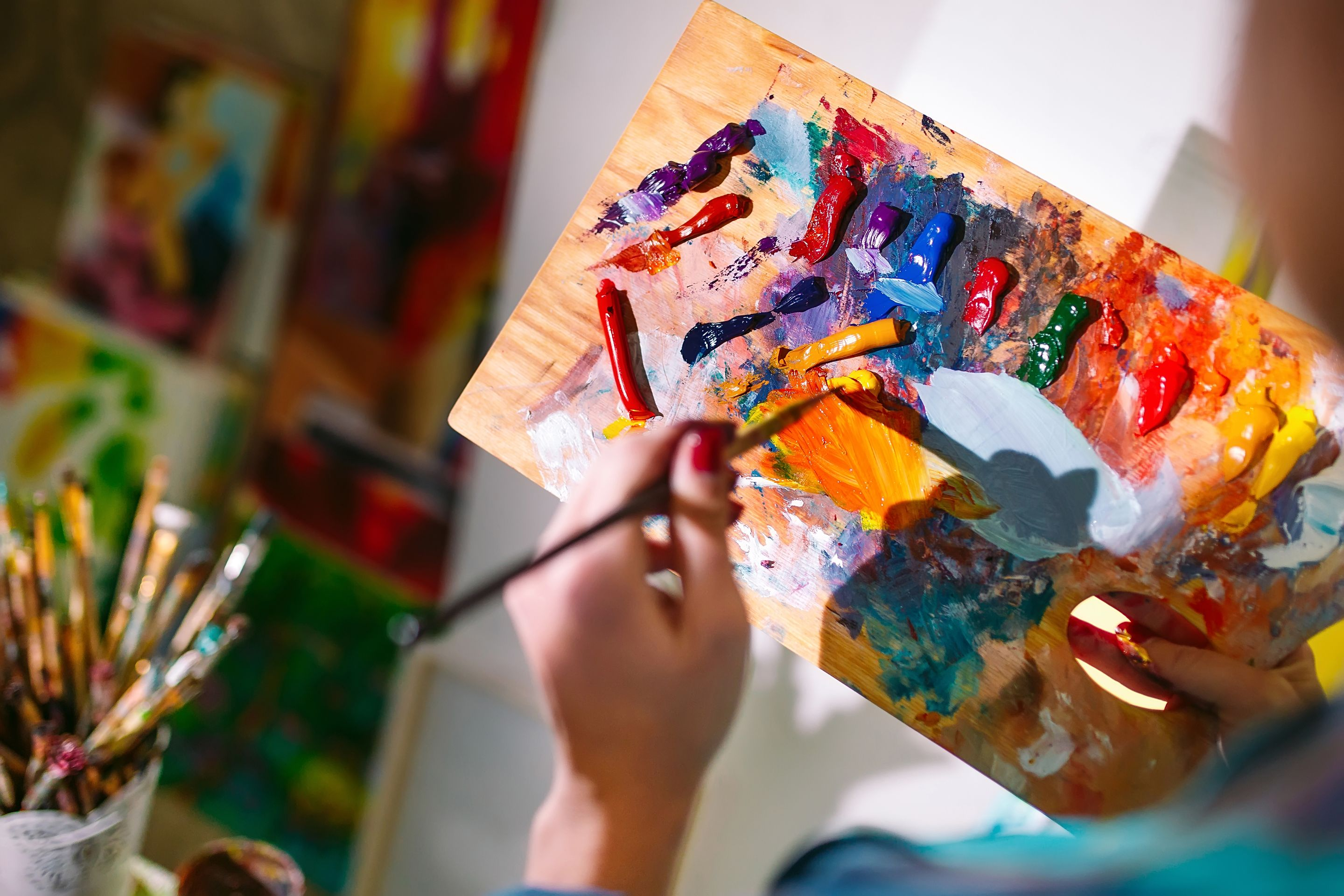 A close-up of a person holding a wooden palette with a variety of acrylic paints on it