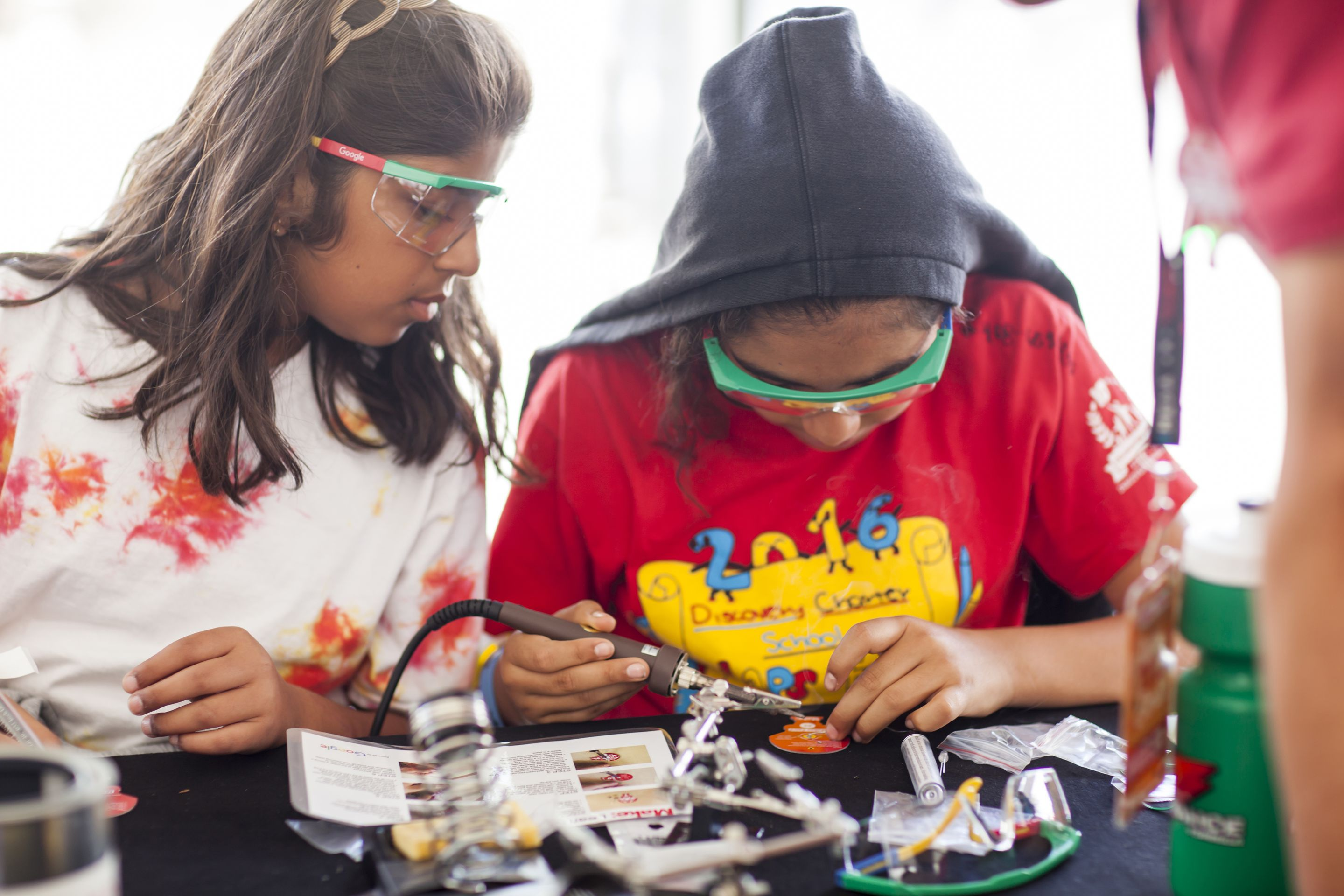 Two middle school students working on a robotics project