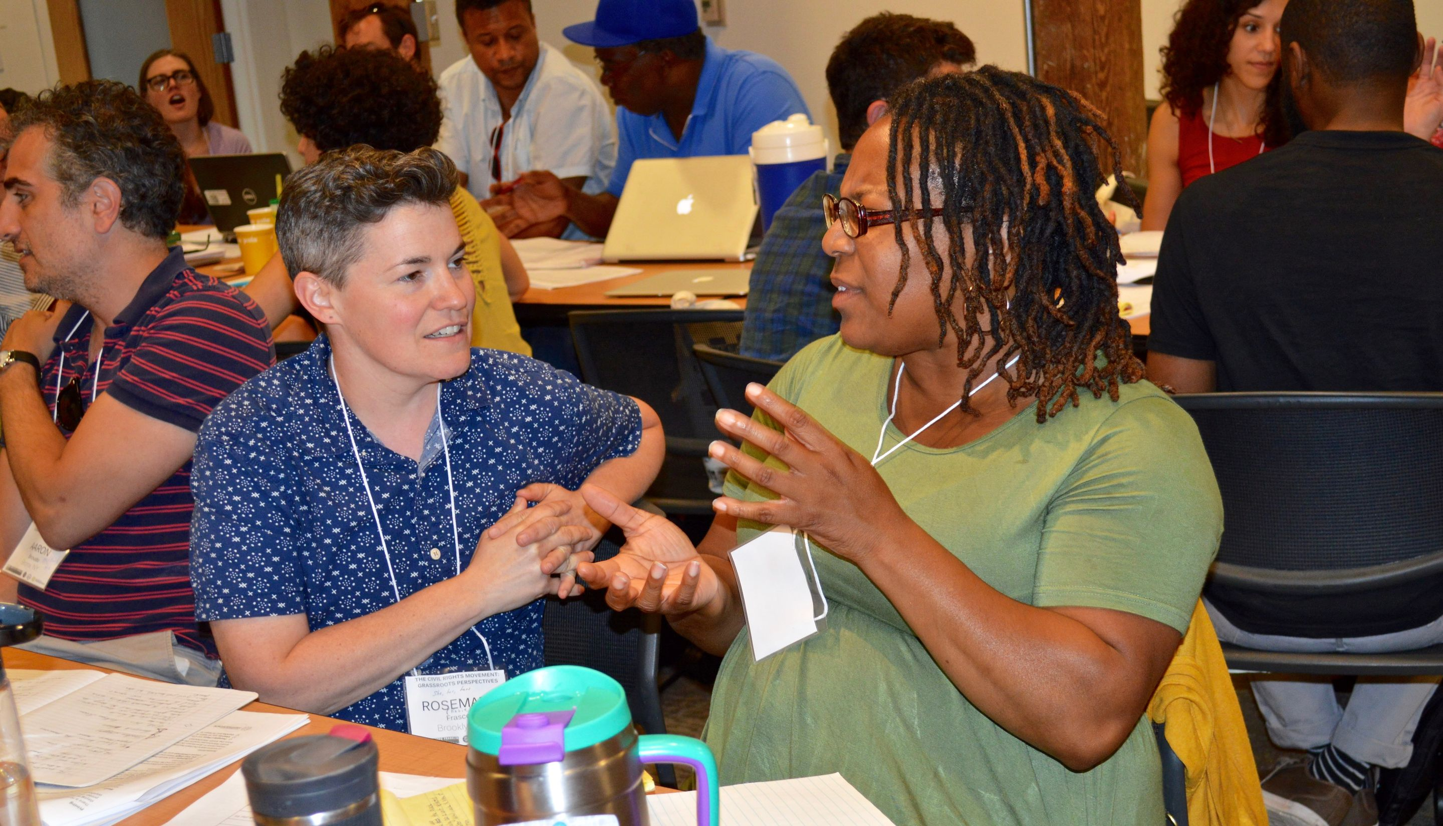 Two teachers discuss lessons at the summer institute.