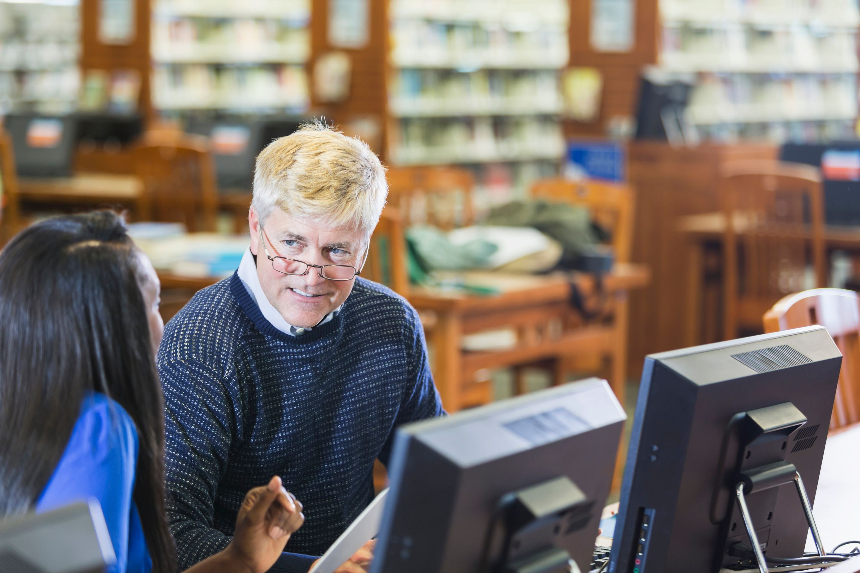 Two teachers talking in a library in front of computer monitors