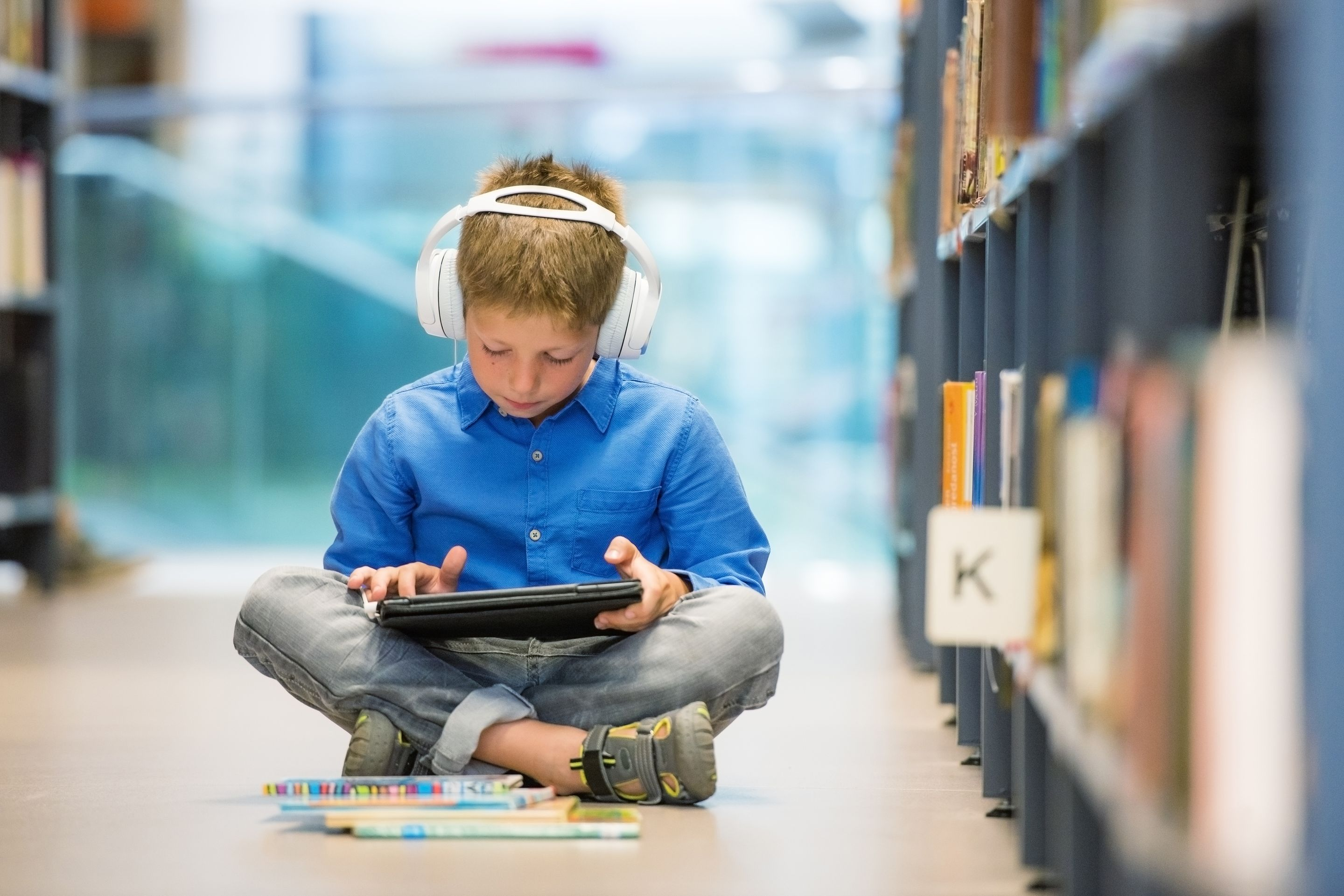An elementary school student sitting on the floor of a library with a tablet and headphones, listening to an audiobook