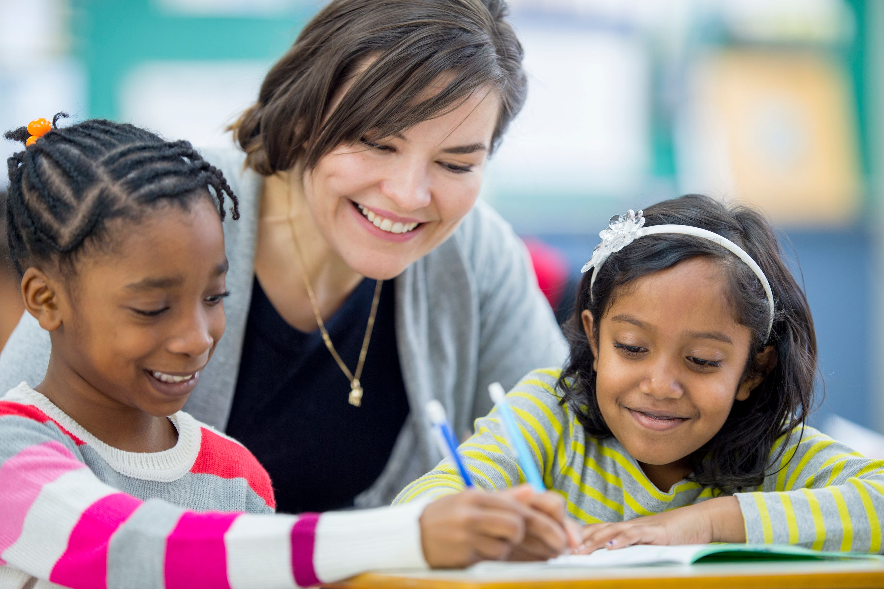 A teacher helping two elementary students with schoolwork