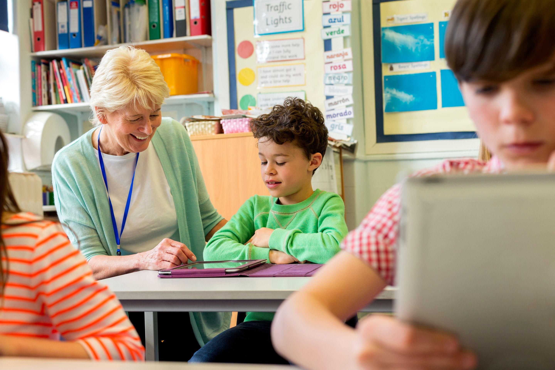 A veteran teacher helping a student in class