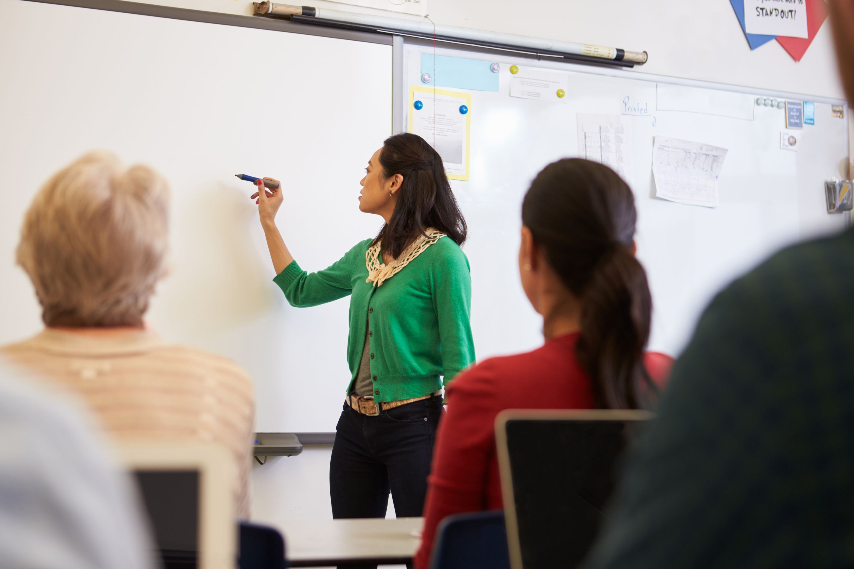 A teacher standing in front of a classroom full of her colleagues. She's writing something on a whiteboard.