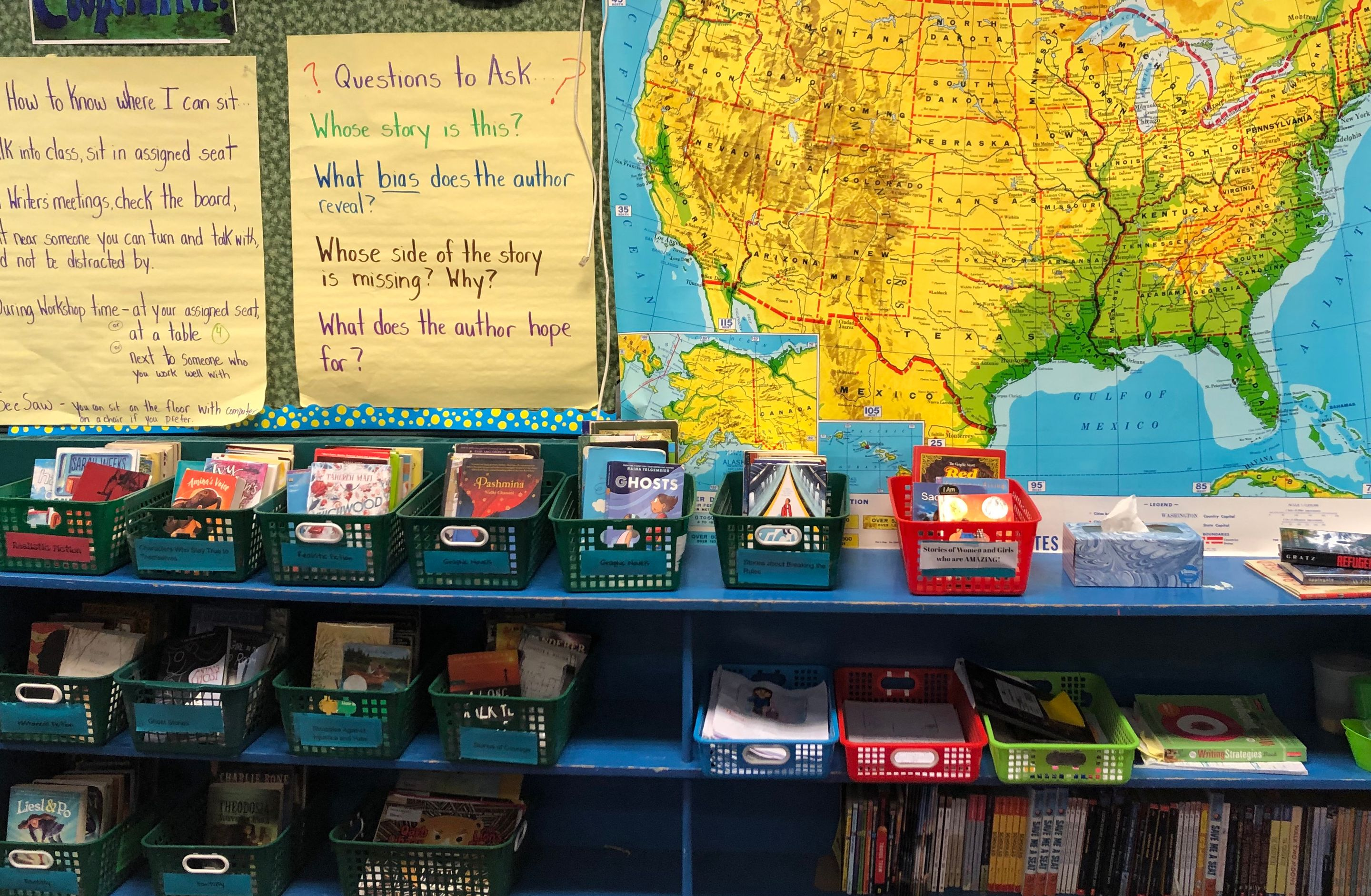 A shelf full of bins of books with a map of the United States behind it