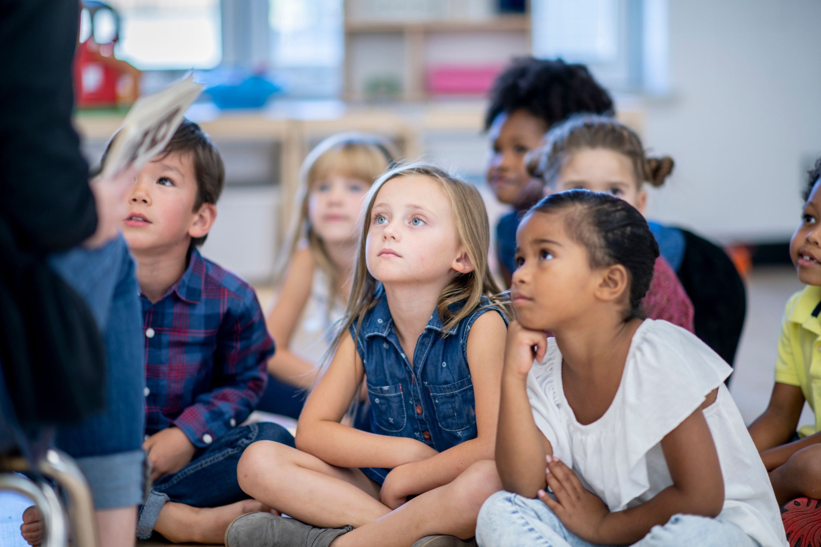 A group of diverse kindergarten students listening to their teacher read a story