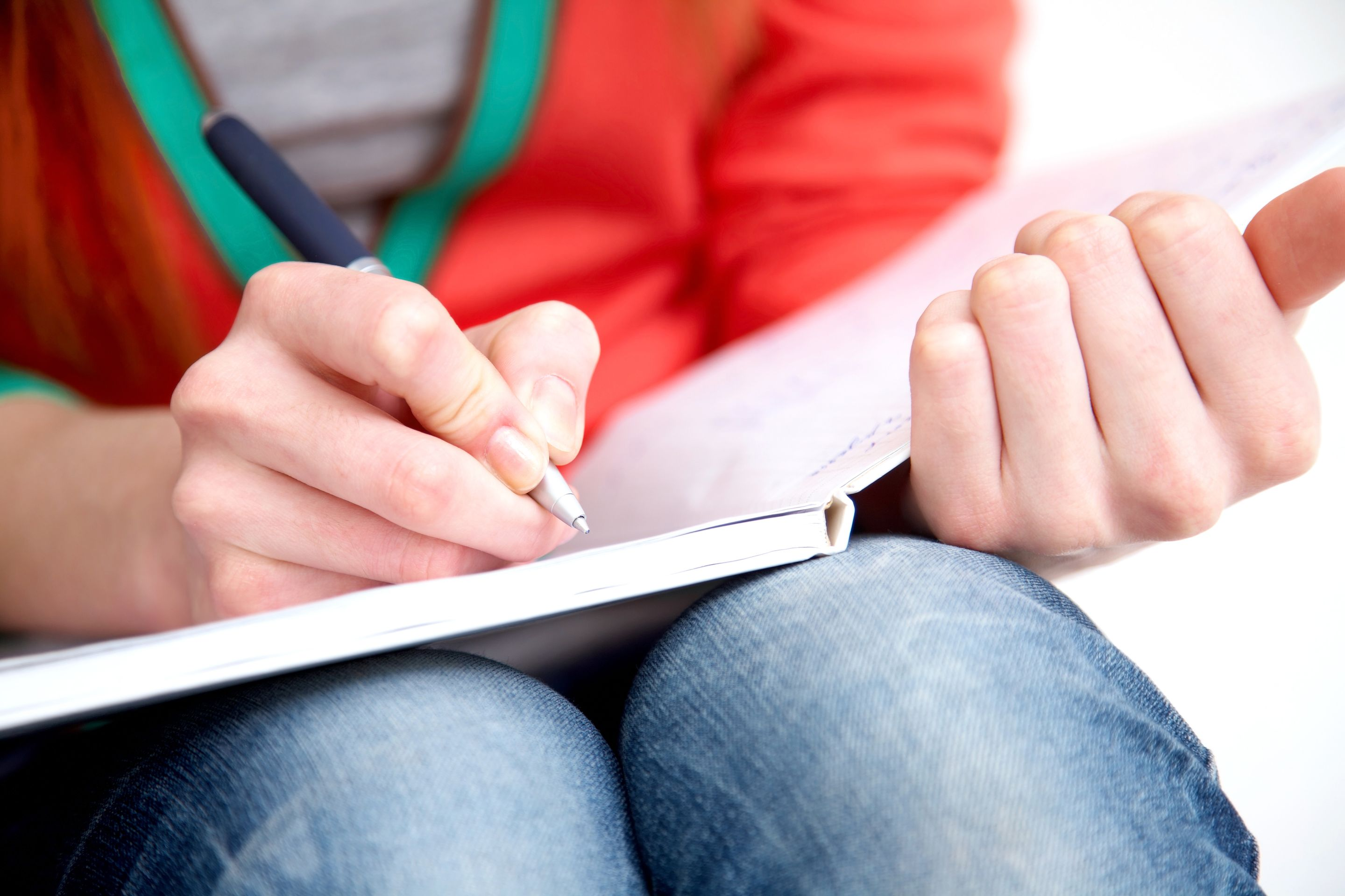 A close-up shot of a teenager writing in a notebook