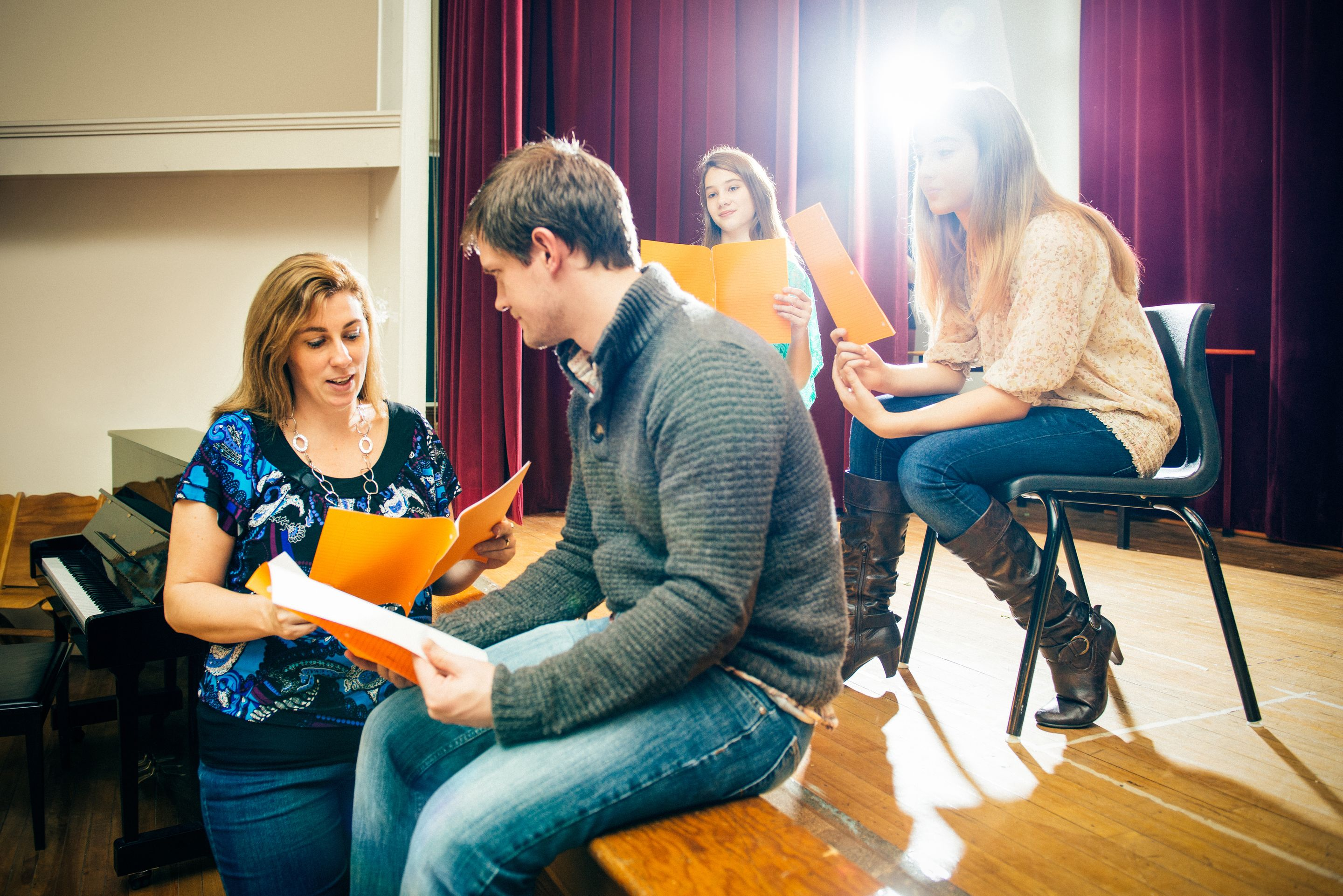 A group of high school students rehearse a scene from a play in a school auditorium