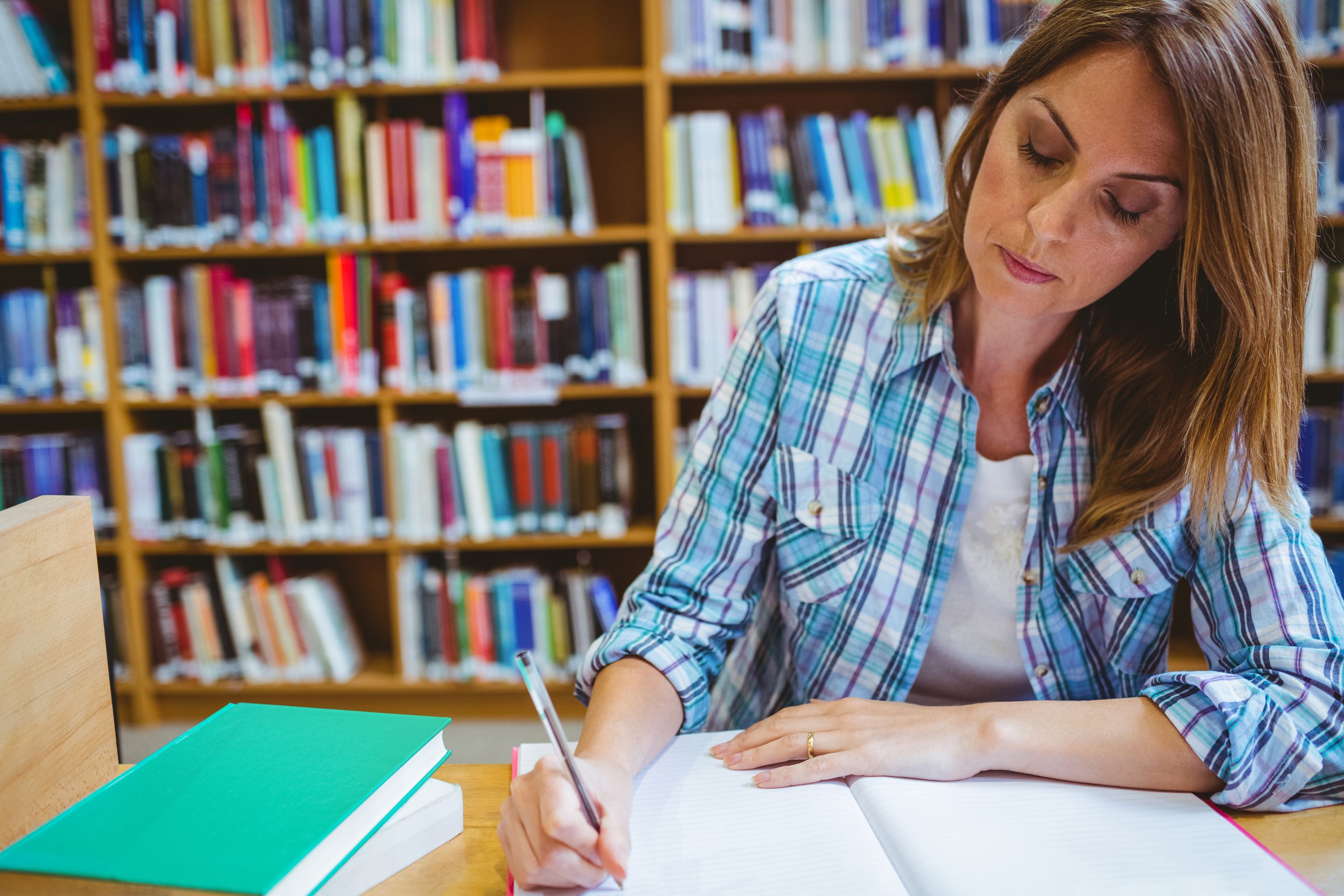 A teacher sitting in the library, writing her thoughts down in a journal