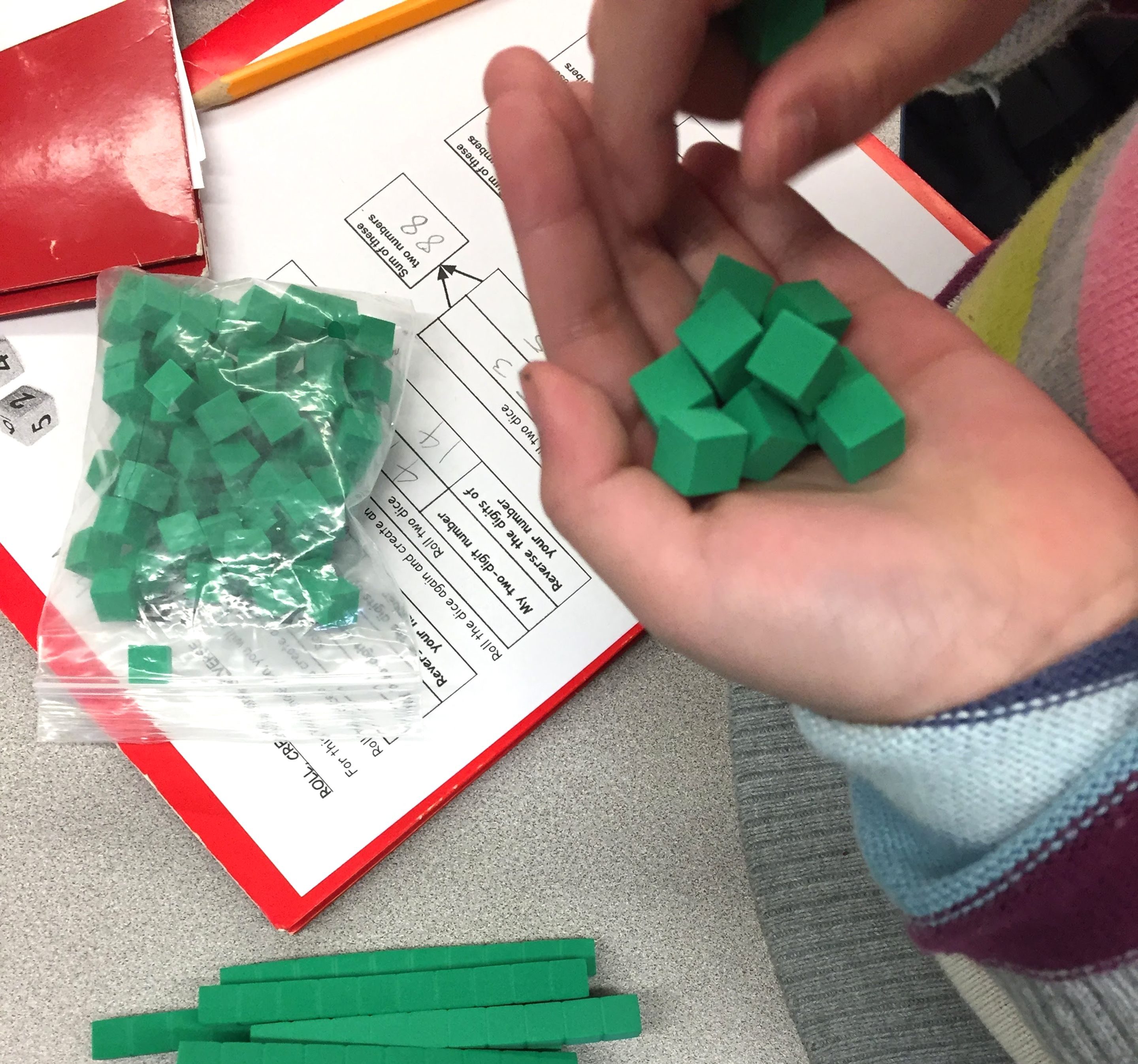 A child's hand holding green base ten blocks for a math game