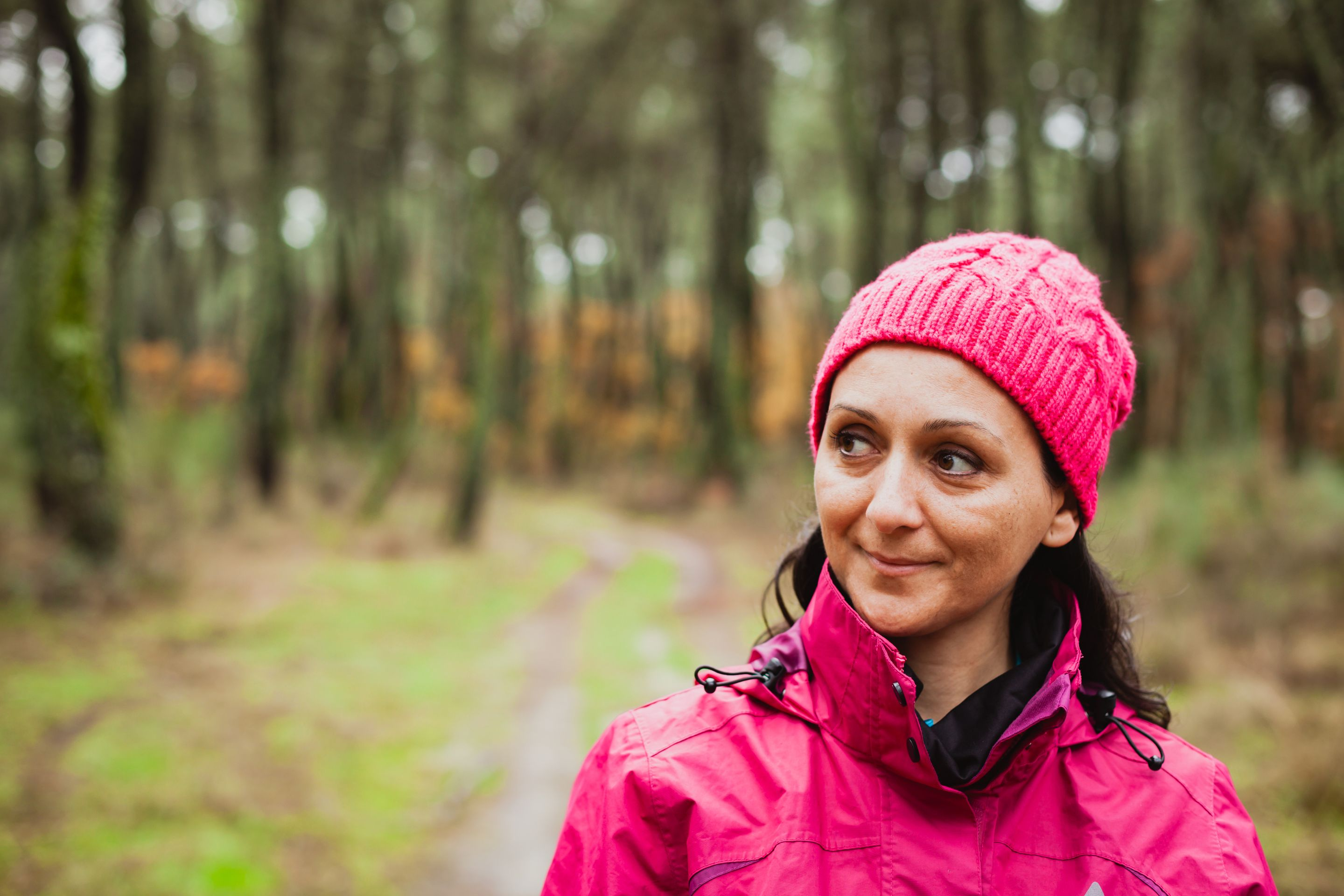 A woman walking through the woods in a pink rain jacket and knit hat