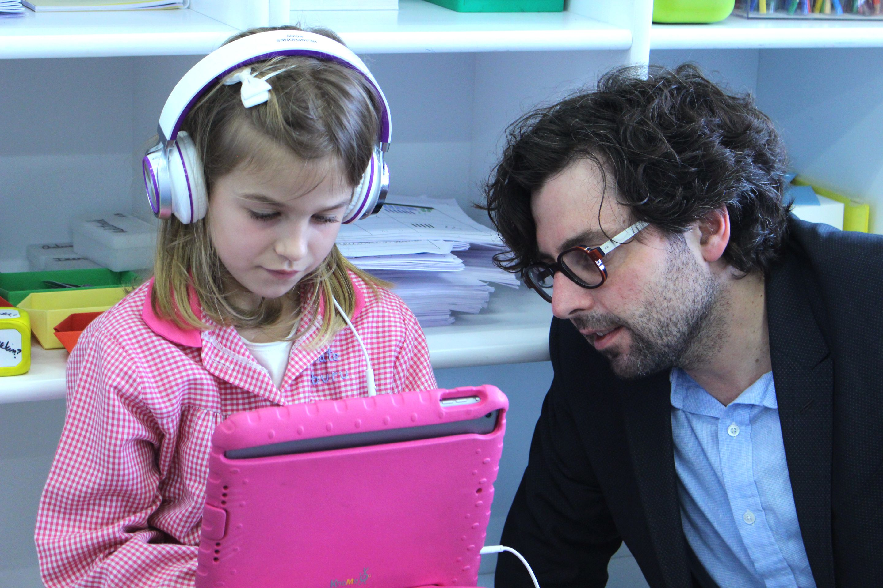 Jordan Shapiro sitting with an elementary student who is using a tablet and wearing headphones