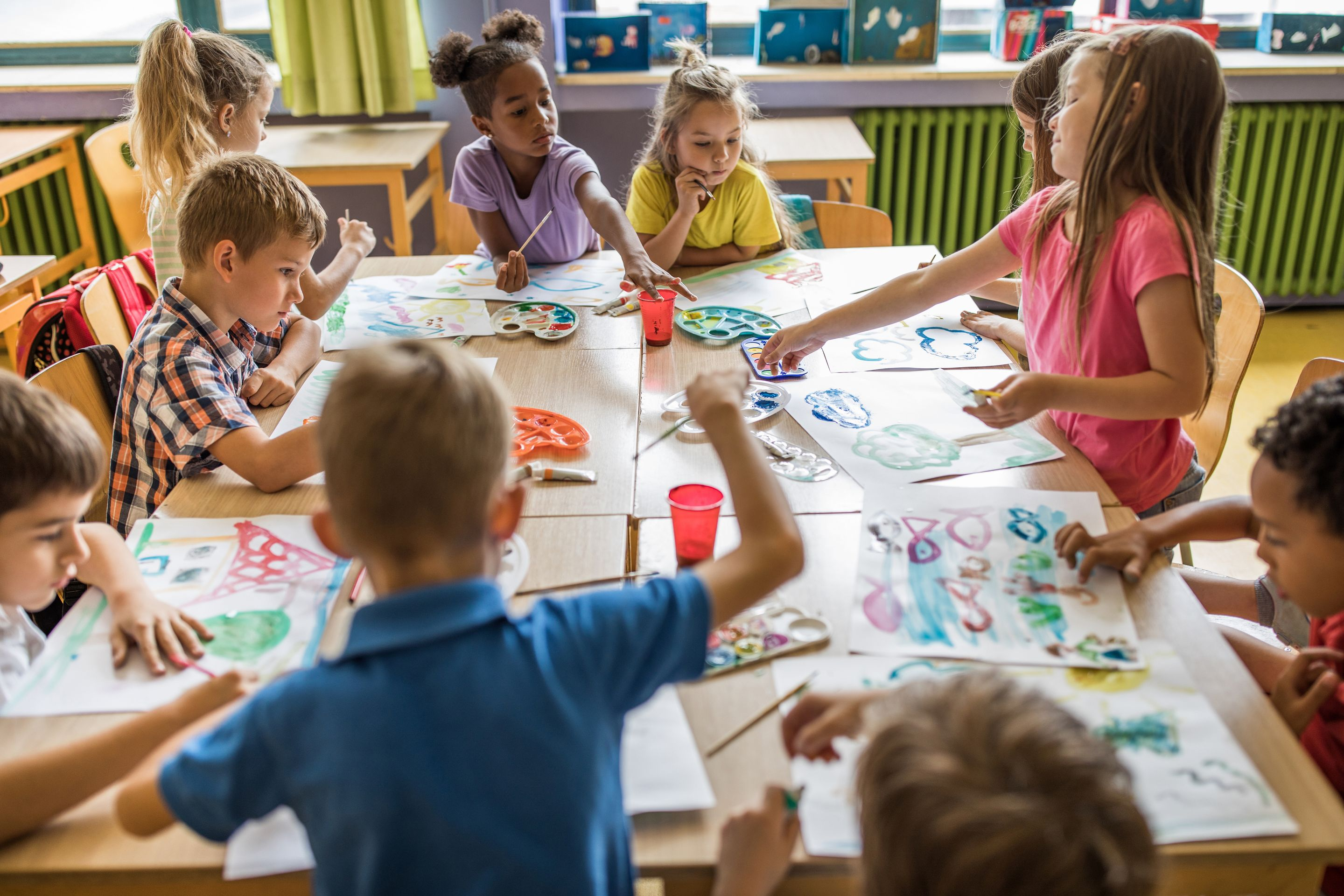 A group of elementary students create art at a large table together in a classroom