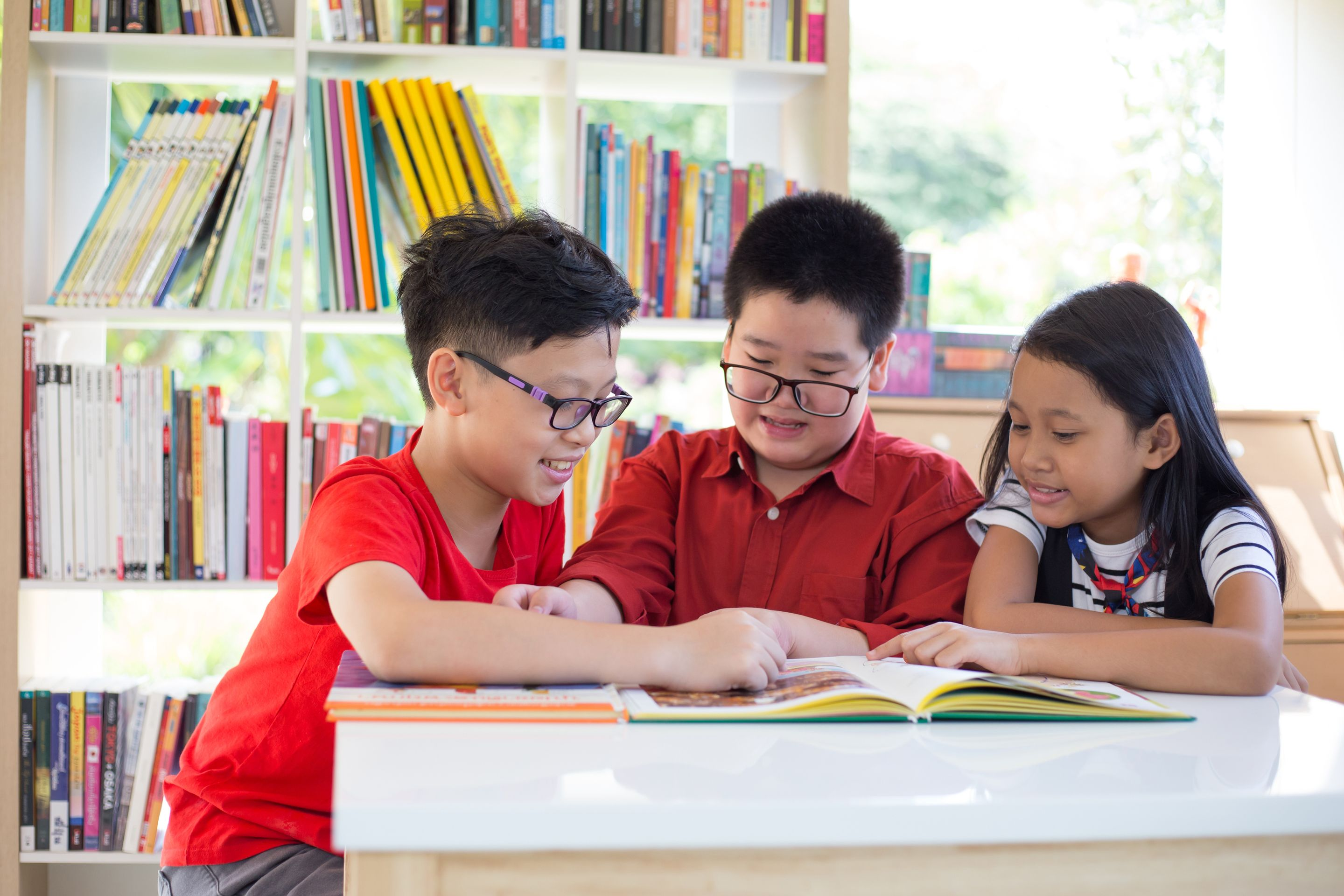 Three elementary students reading together in a library