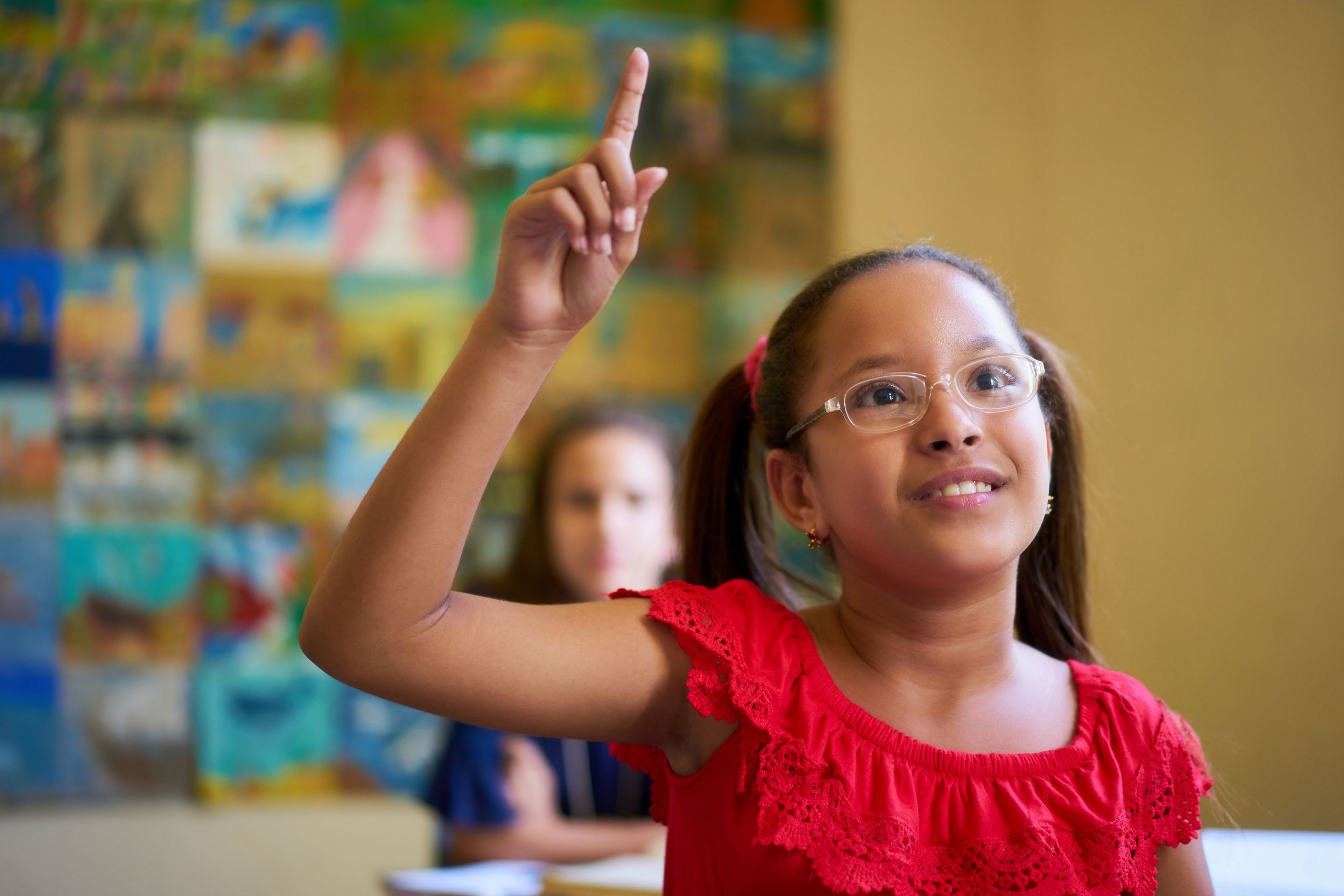 An elementary student raising her hand in class