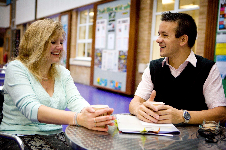 Two teachers talking in a school common area