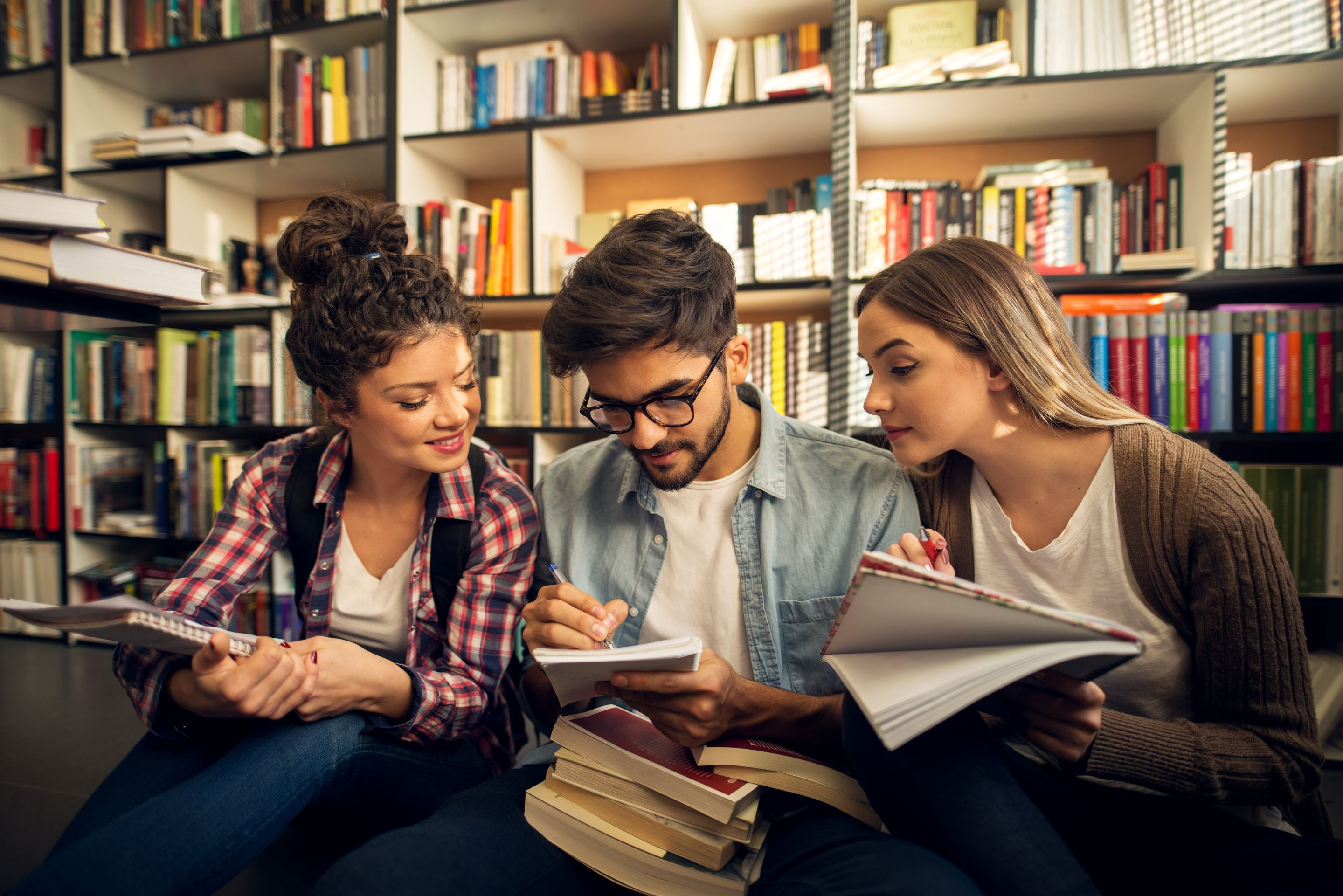Three high school students reading and taking notes in a library