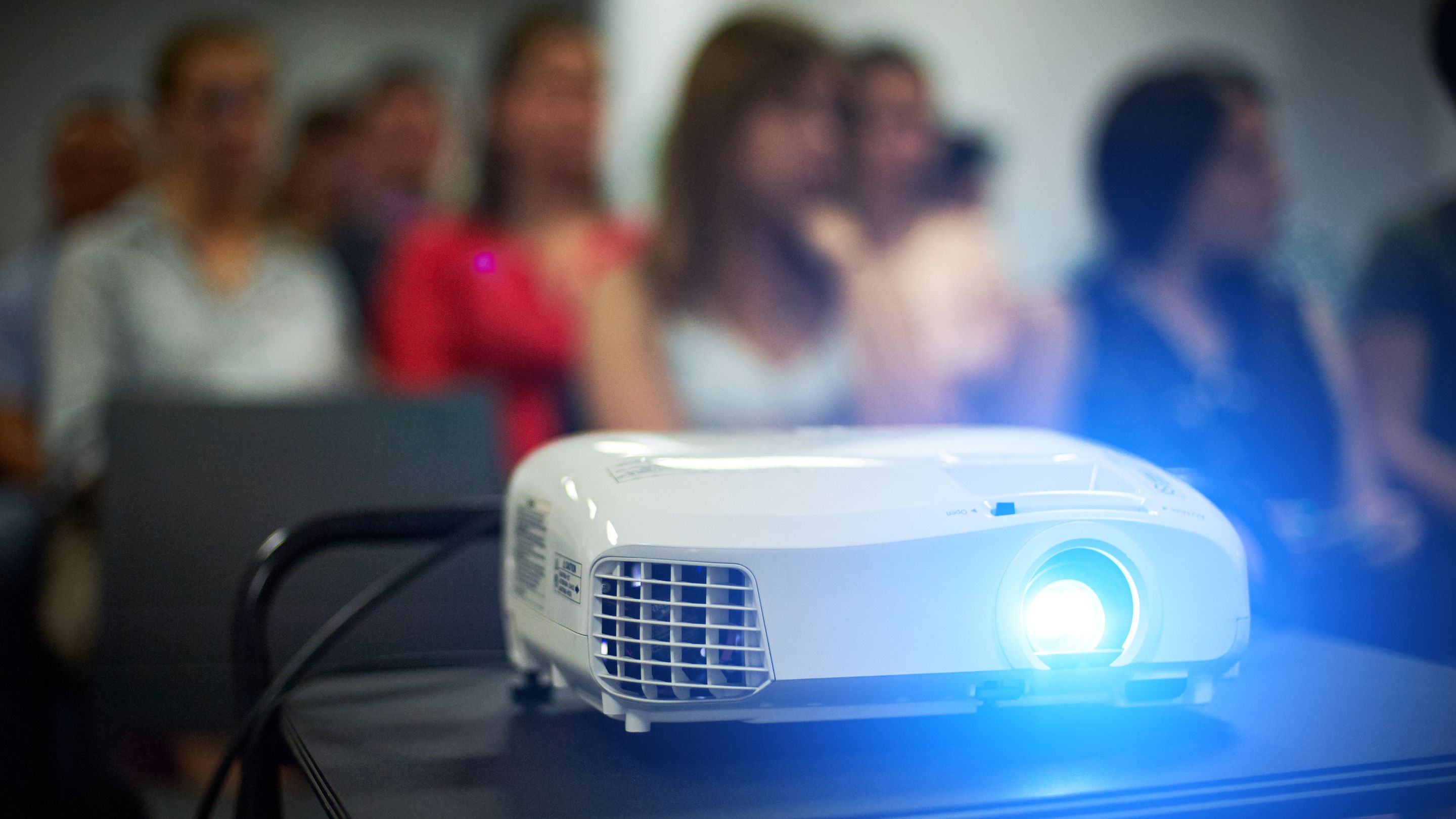A video projector sitting on a cart, displaying something in front of a group of students