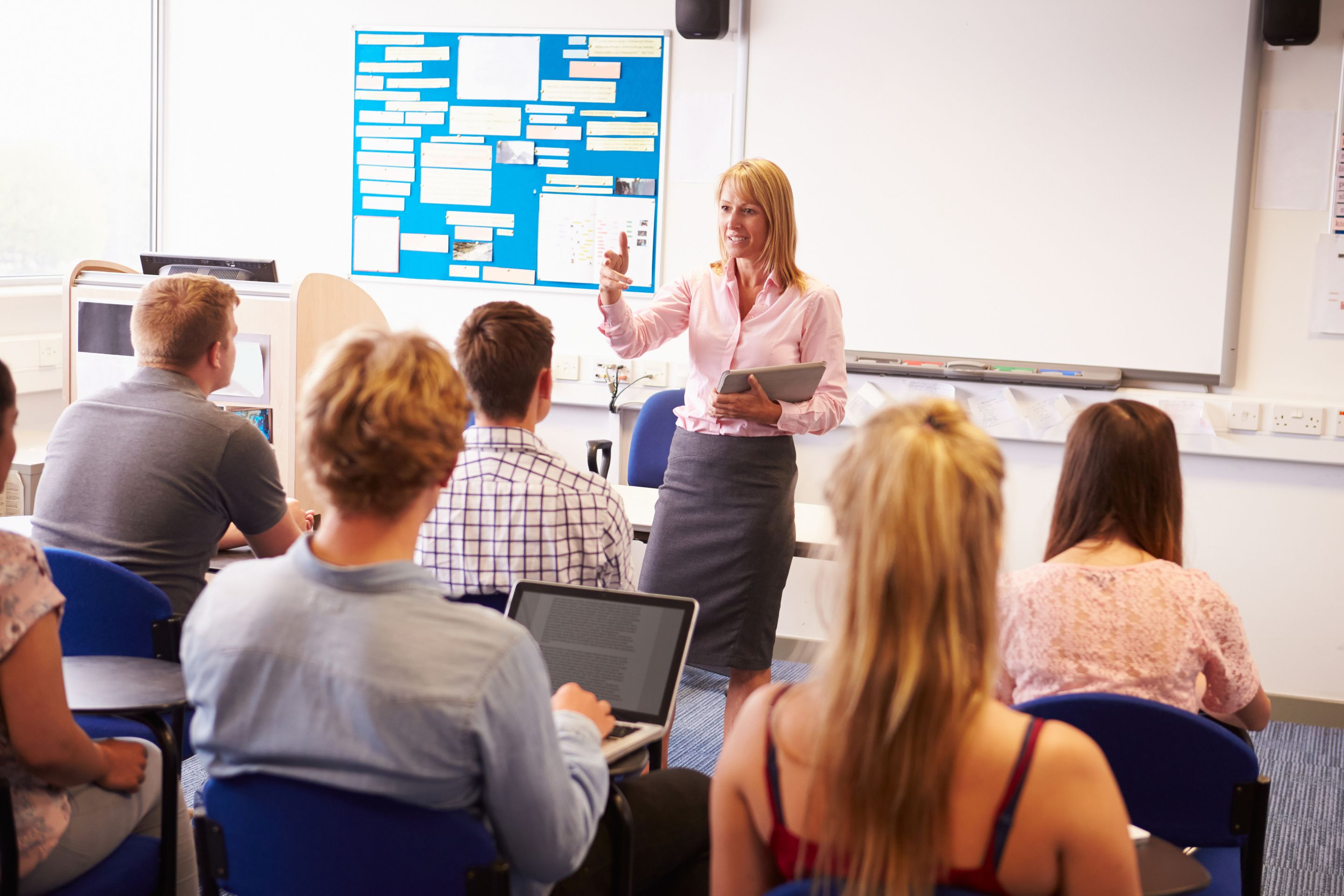 A teacher at the front of a classroom, responding to a student's question