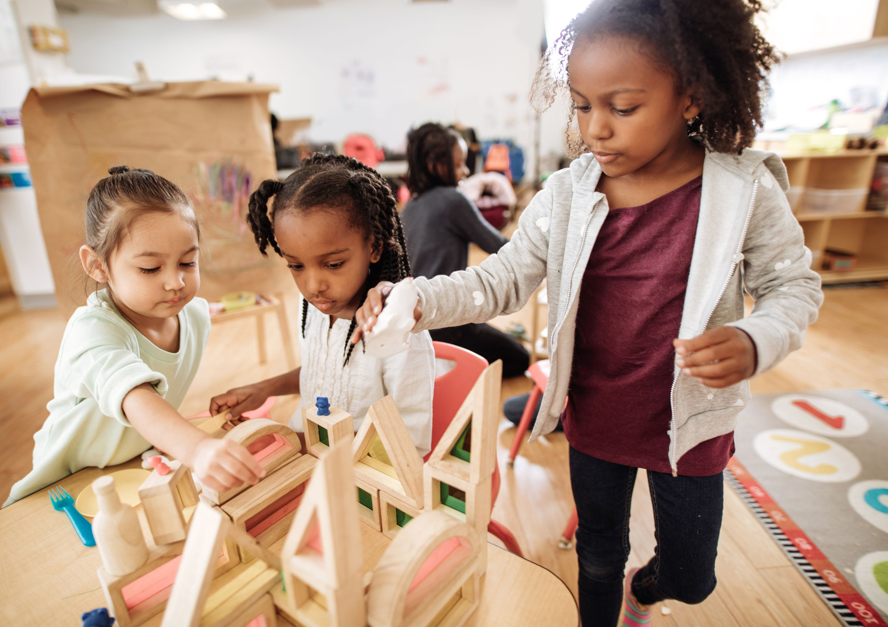A group of young children building a house out of blocks together in a classroom