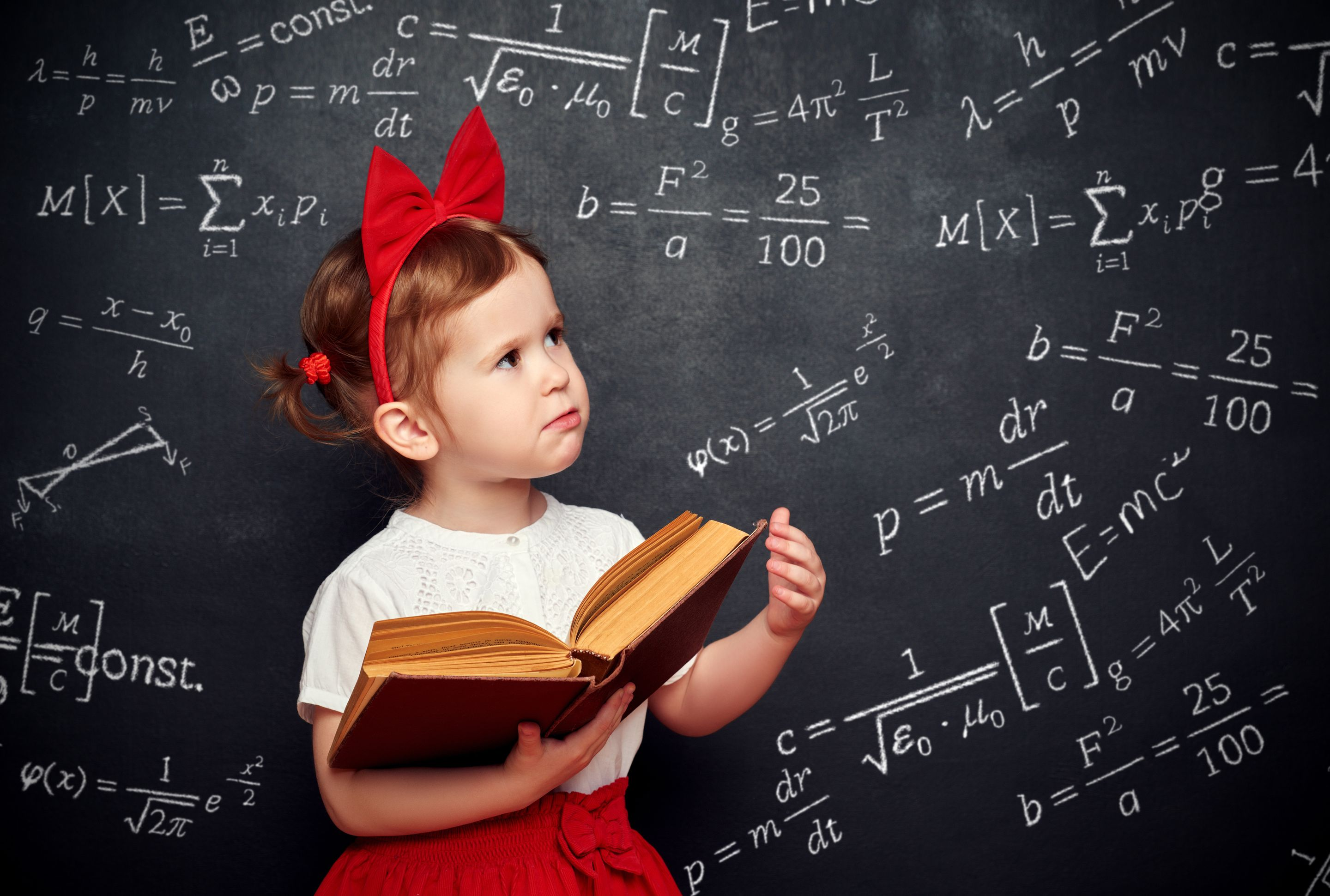 A toddler in a red and white outfit holding an open book in front of a blackboard covered in advanced math formulas
