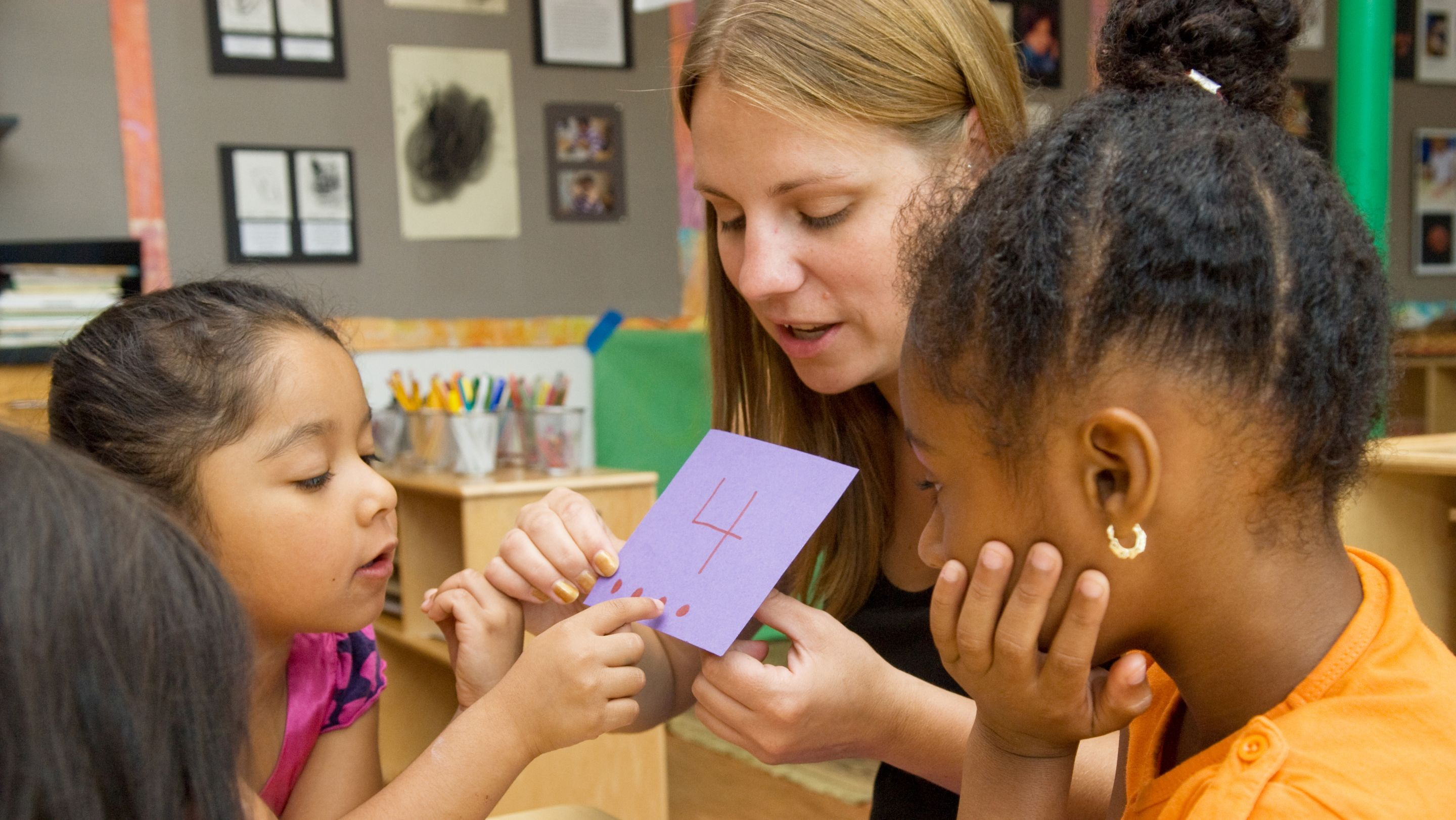 A teacher shows young students a purple construction paper card with the number 4 on it