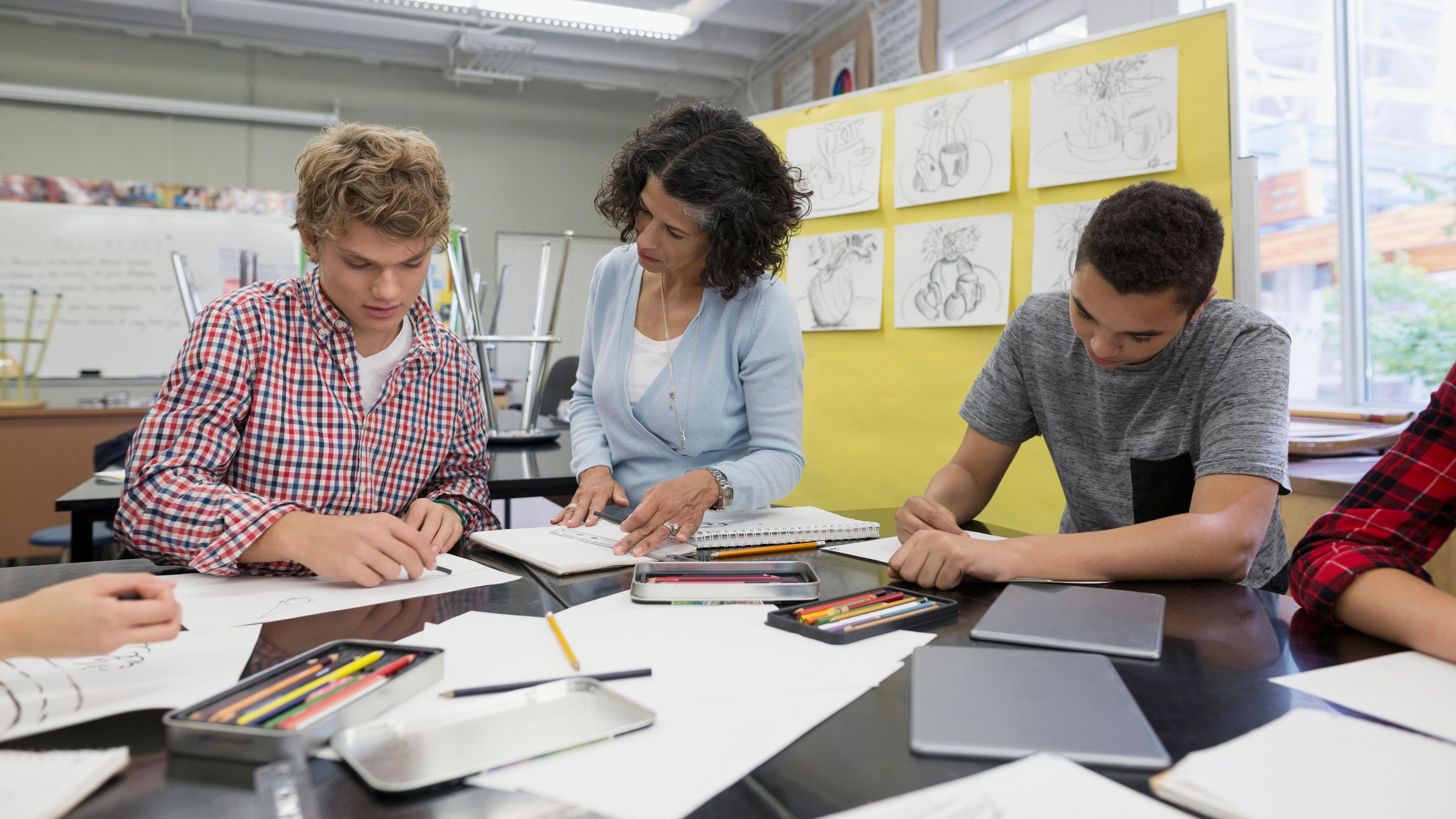 A teacher helping two high school art students with their sketches