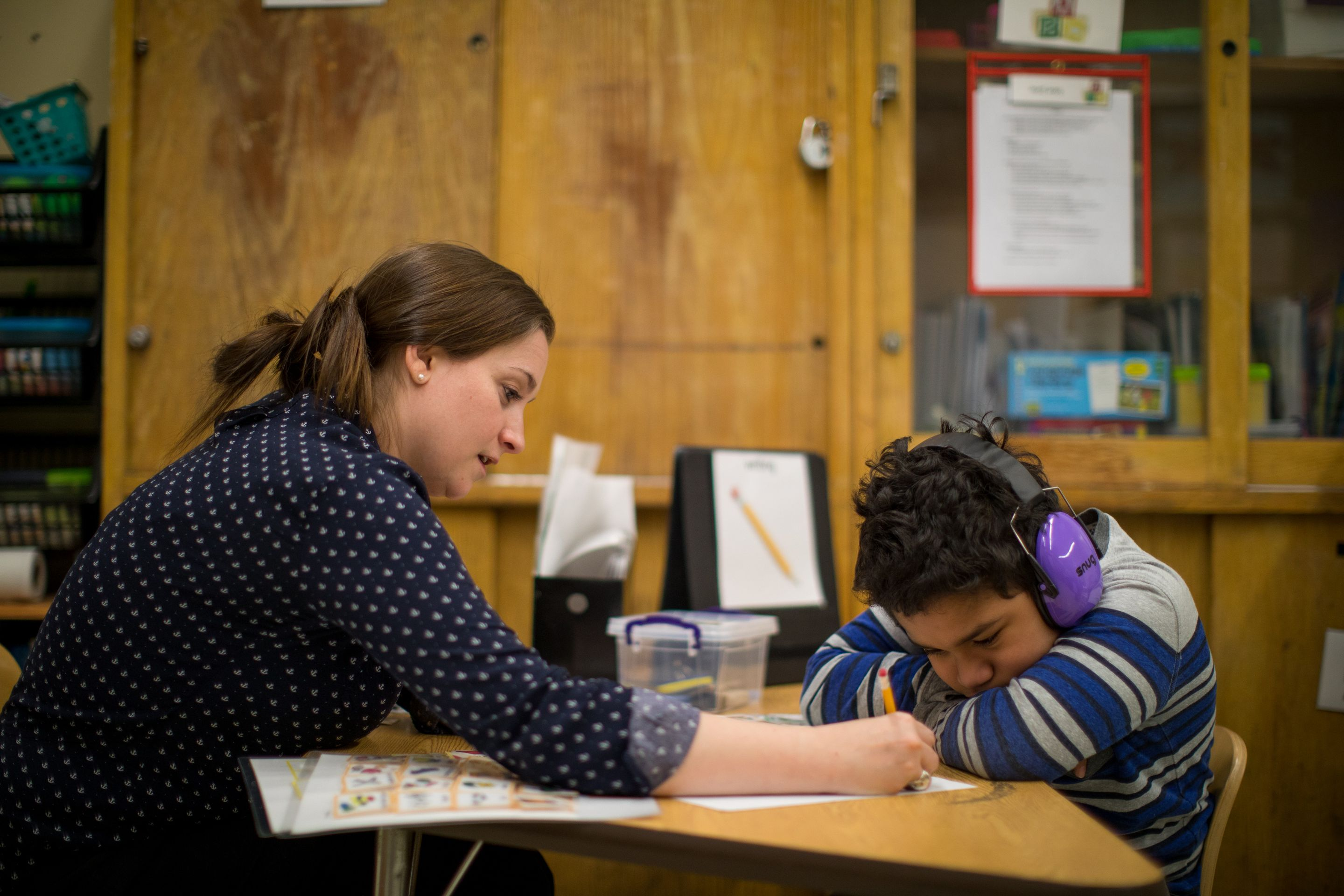 Teacher Katie Papaccioli works with an autistic student who wears noise-canceling headphones due to sound sensitivities.
