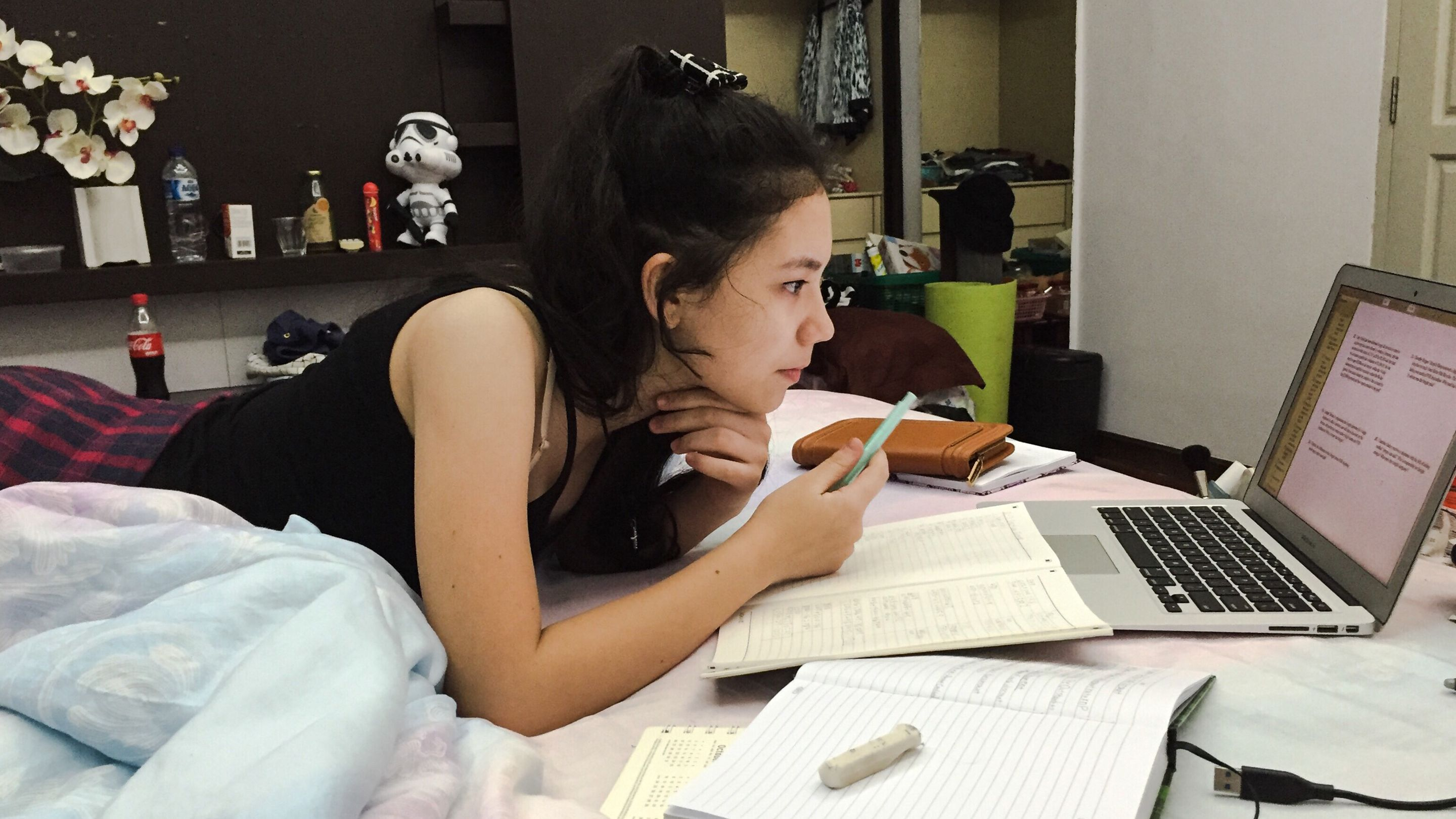 A student studying on her bed with a laptop, textbooks, and notebooks