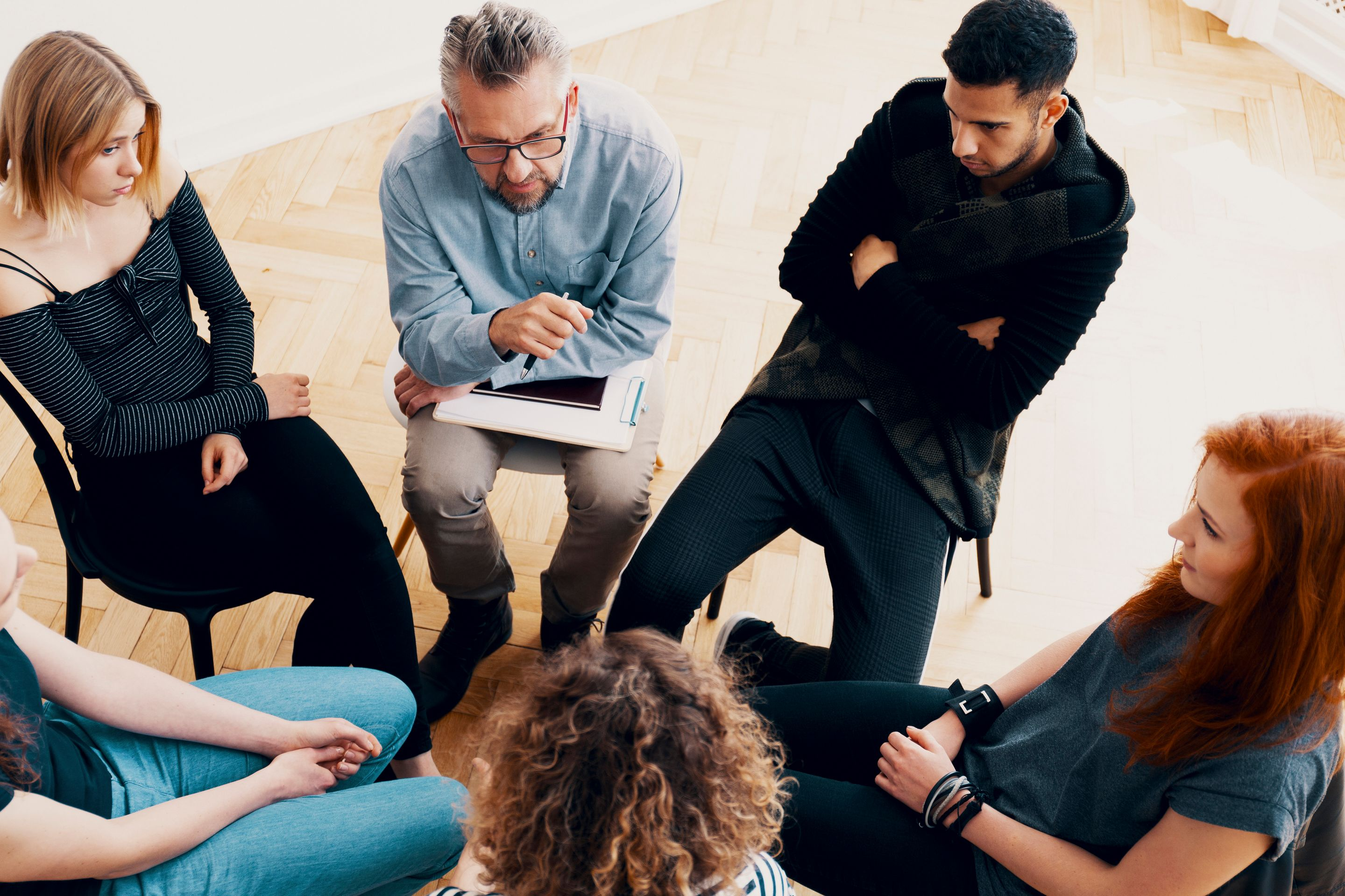 A group of students and their teacher sitting in a circle, talking about a serious subject