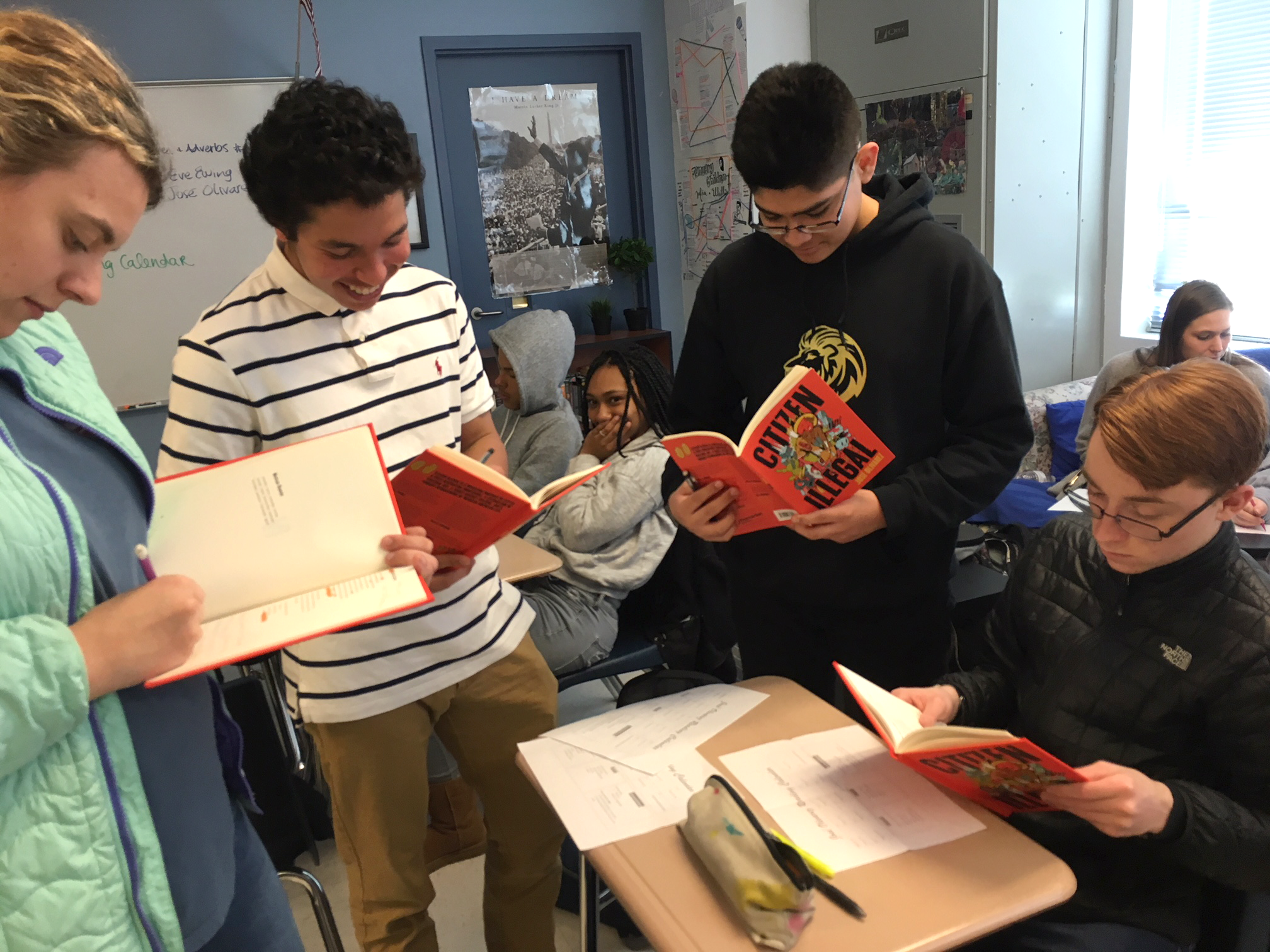 A group of teens in a classroom reading a poetry book titled Citizen Illegal by Jose Olivarez