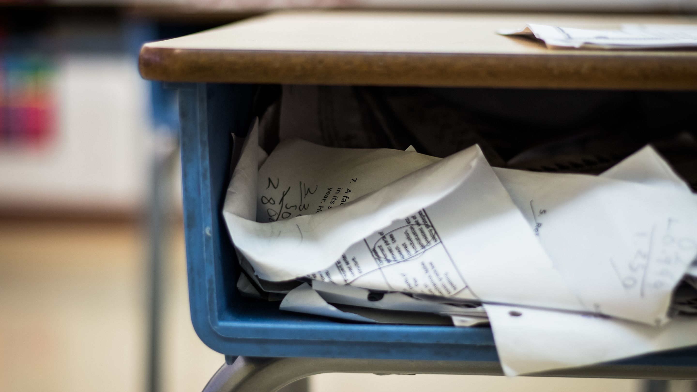 A messy school desk with papers spilling out of it
