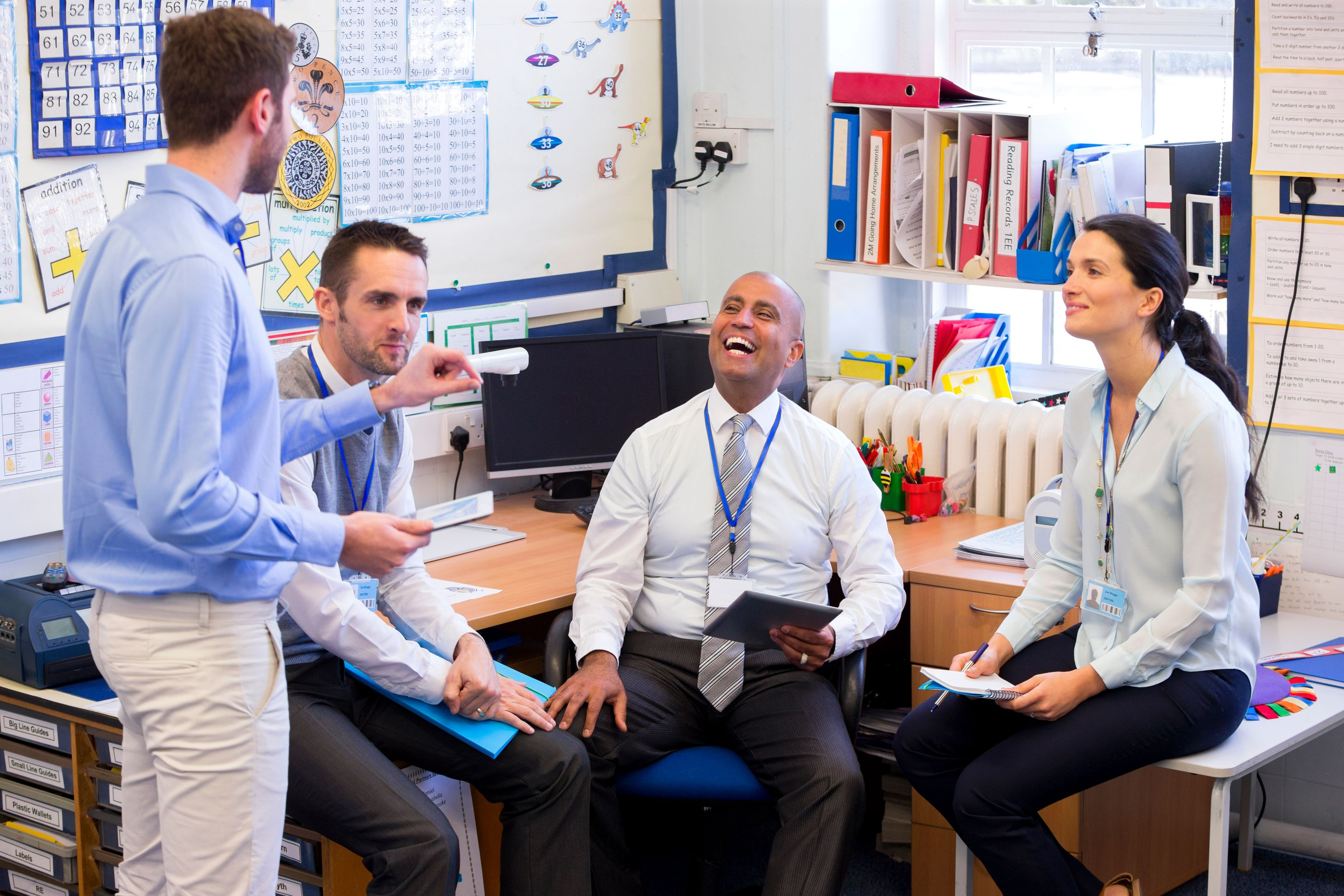School teachers gather in a small school office for a chat.
