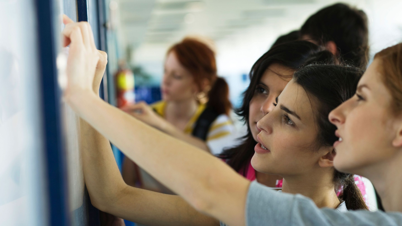 High school students examining work on a bulletin board in a classroom