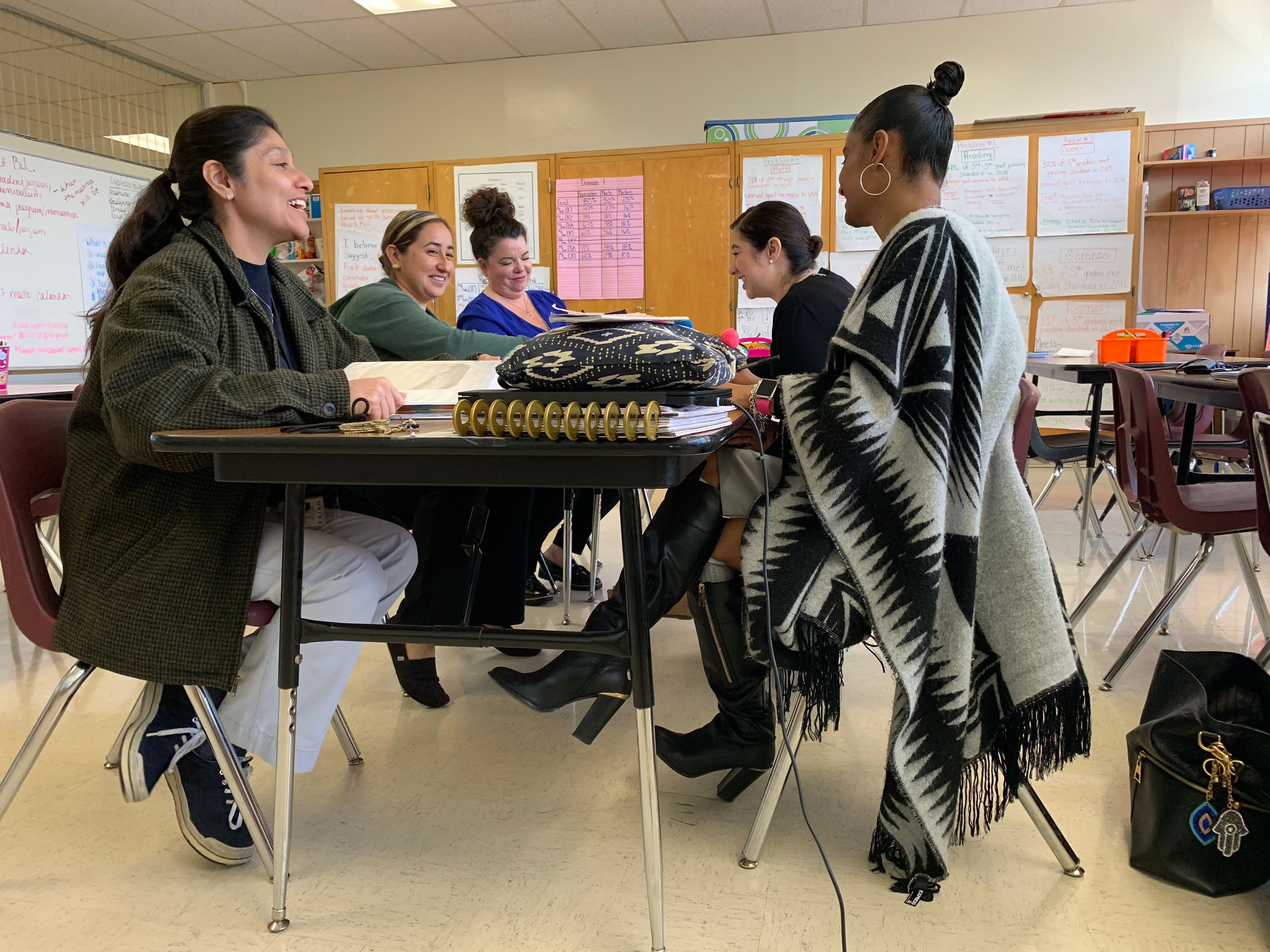 "Principal Sonya Mora (right) and her teachers discuss their students in their school's ""war room."""