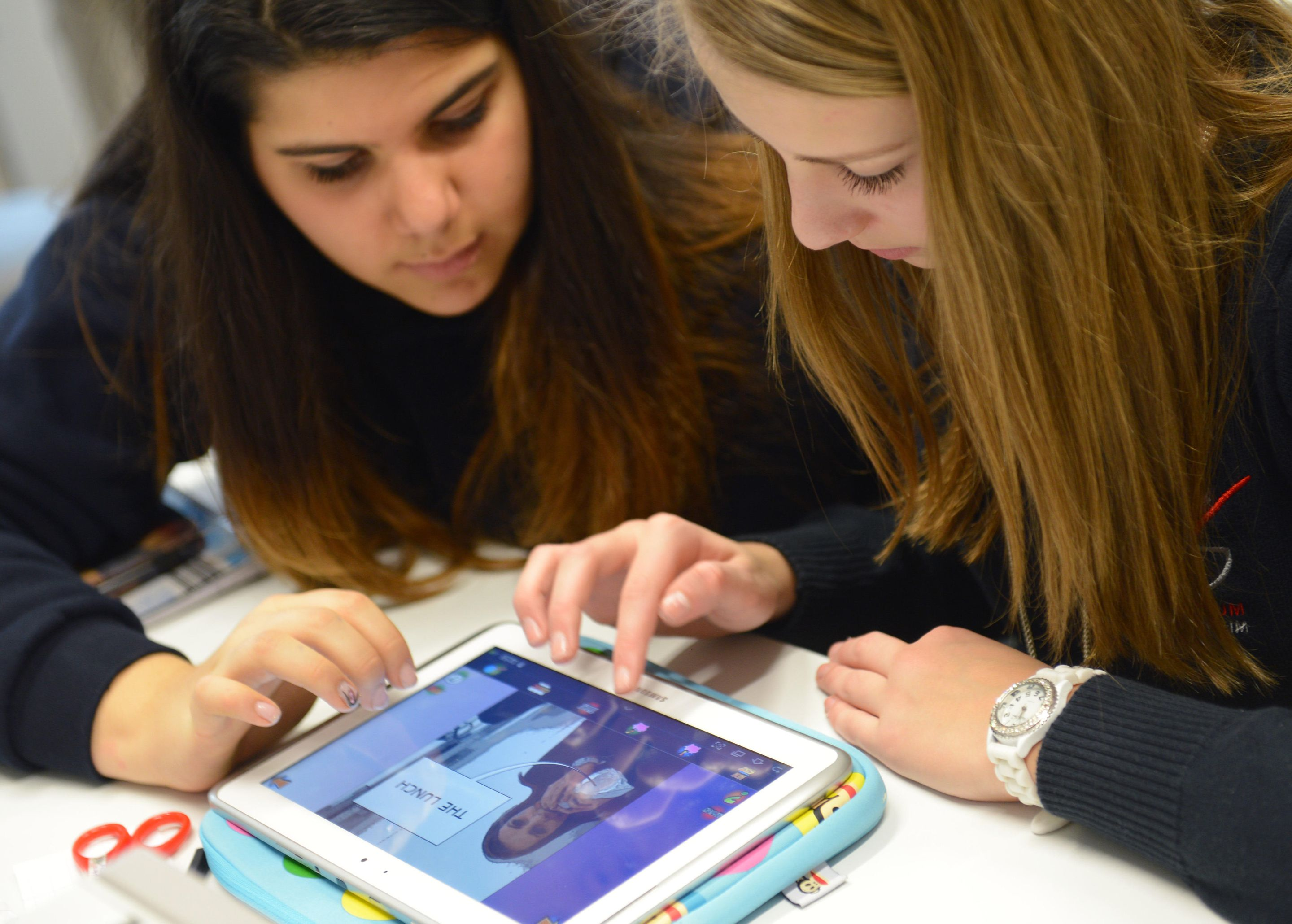 Two female high school students working together on a tablet