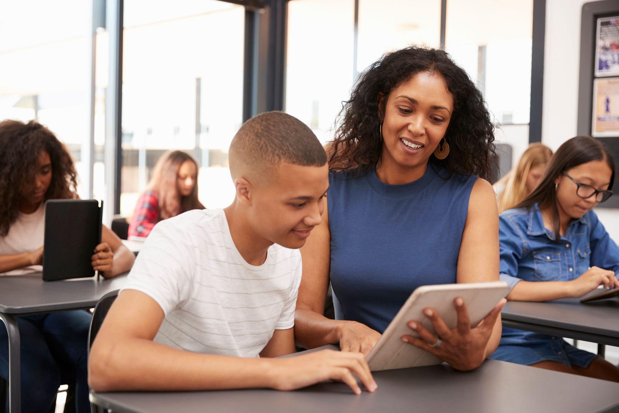 A teacher helps a teenage student