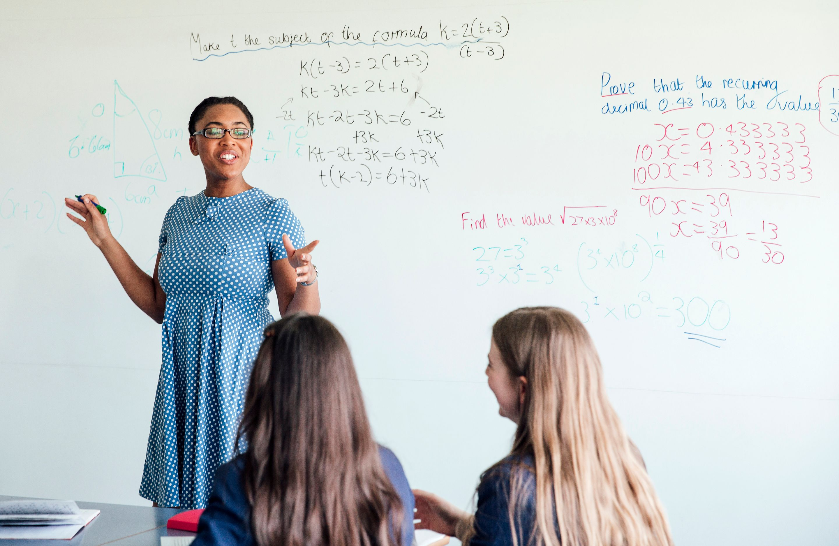 Teacher standing in front of a white board instructing students