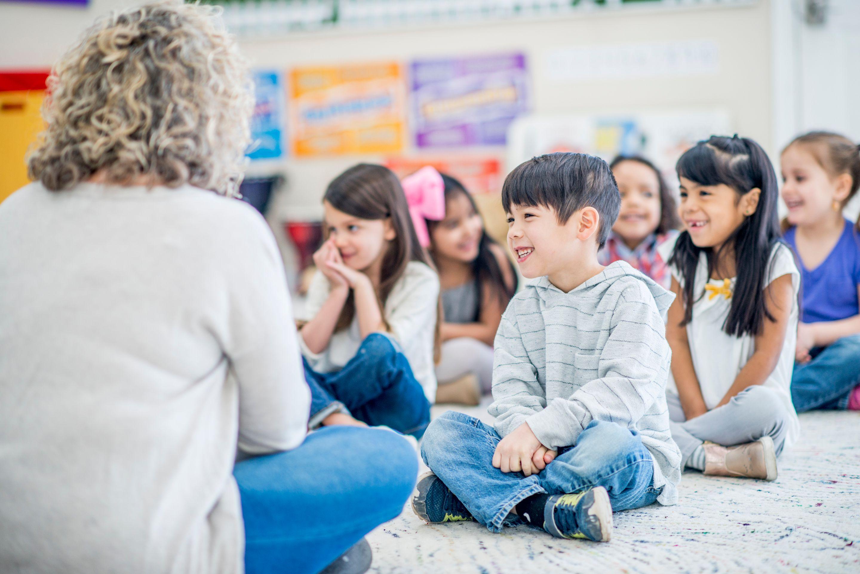 Kids gathered around listening to a story.