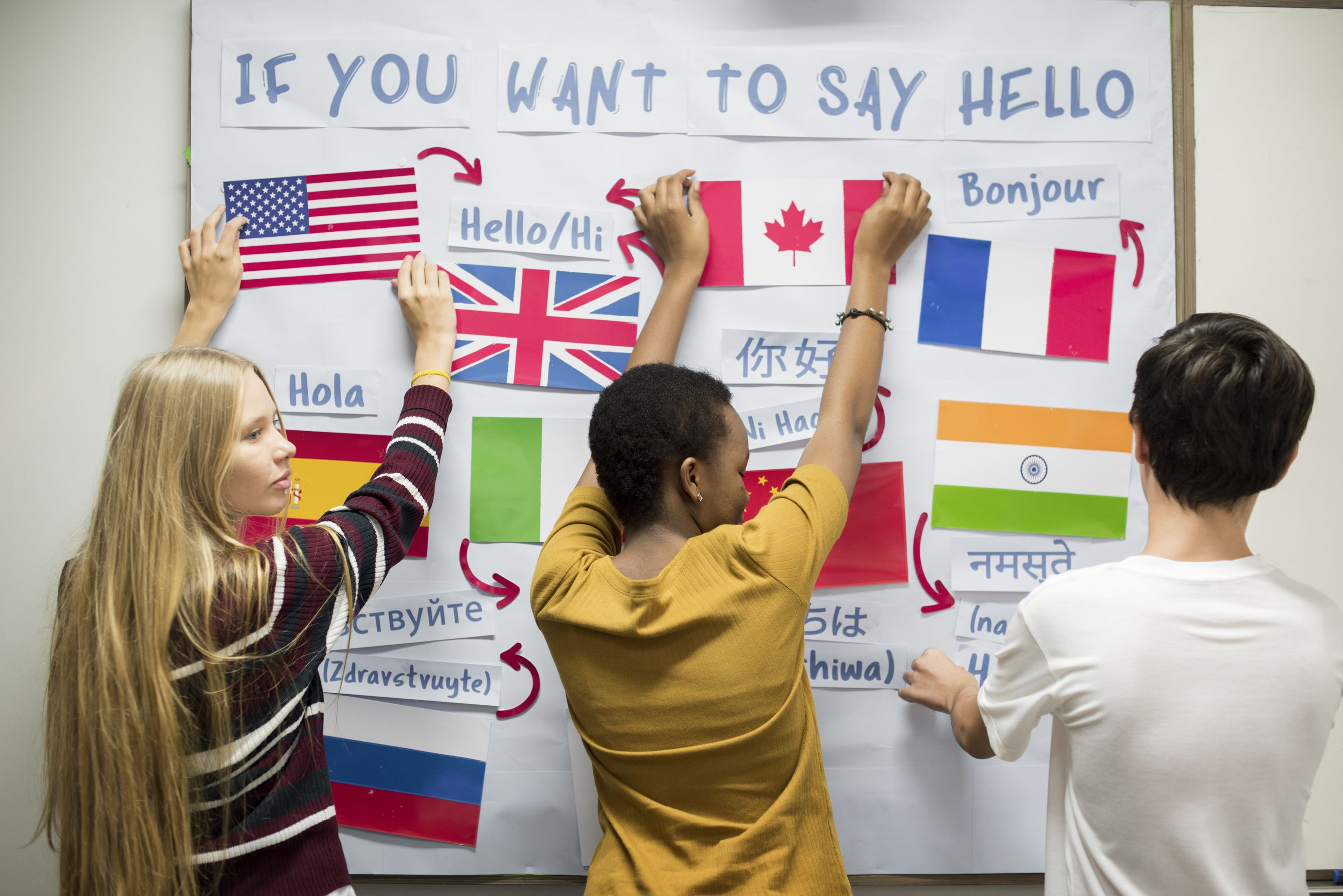 Three high school students working together on a foreign language activity
