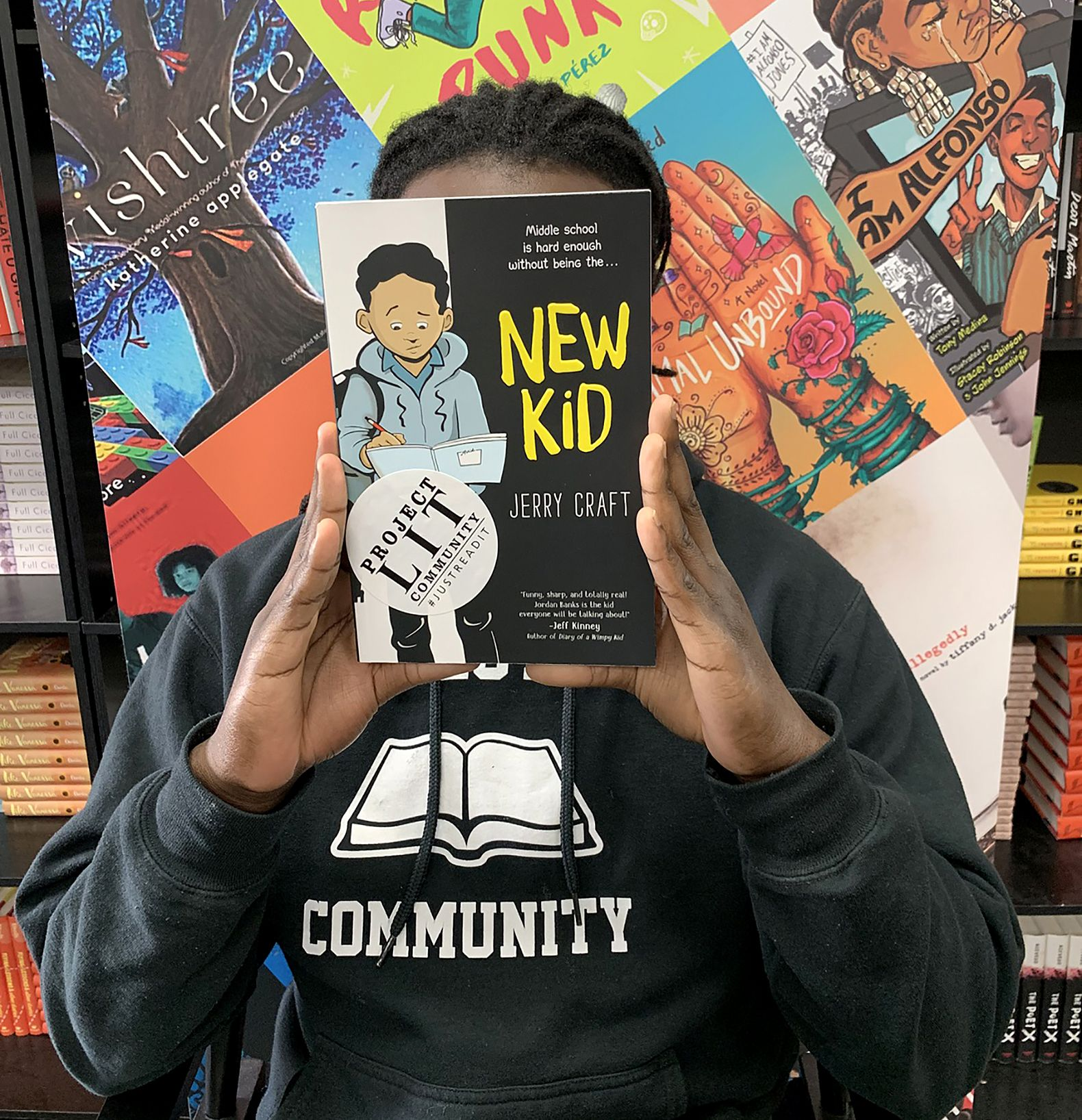 A student holds up a book from the school library