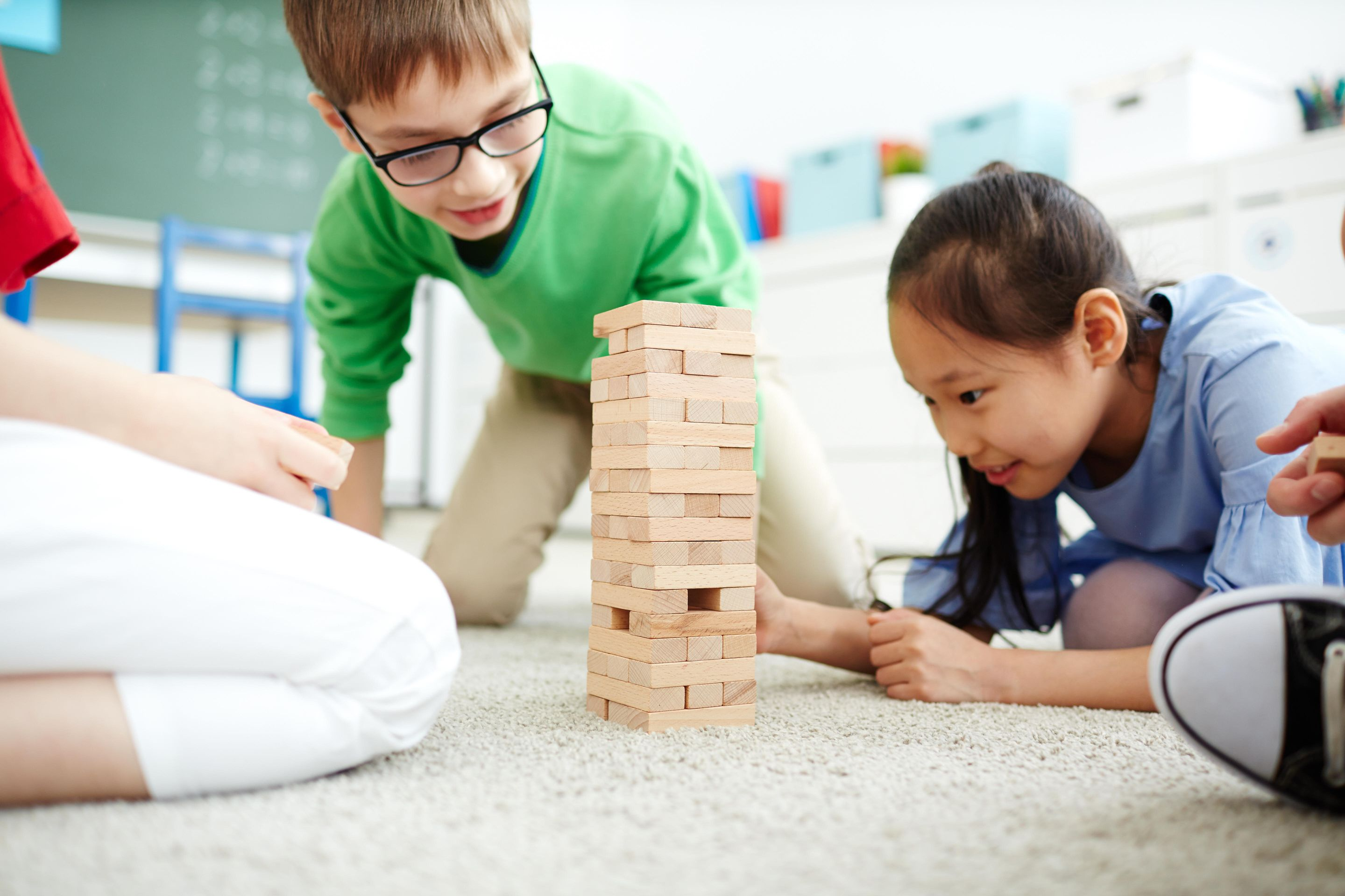 A group of elementary school students playing Jenga.