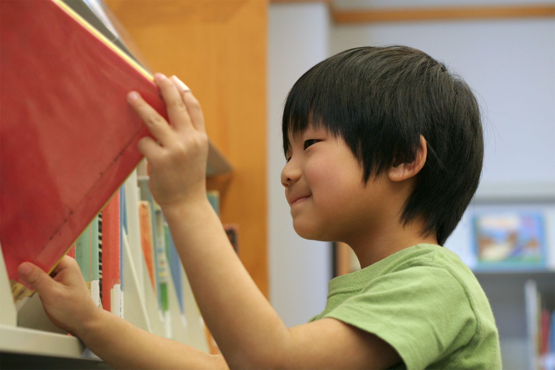 Elementary school student putting a book away on a shelf