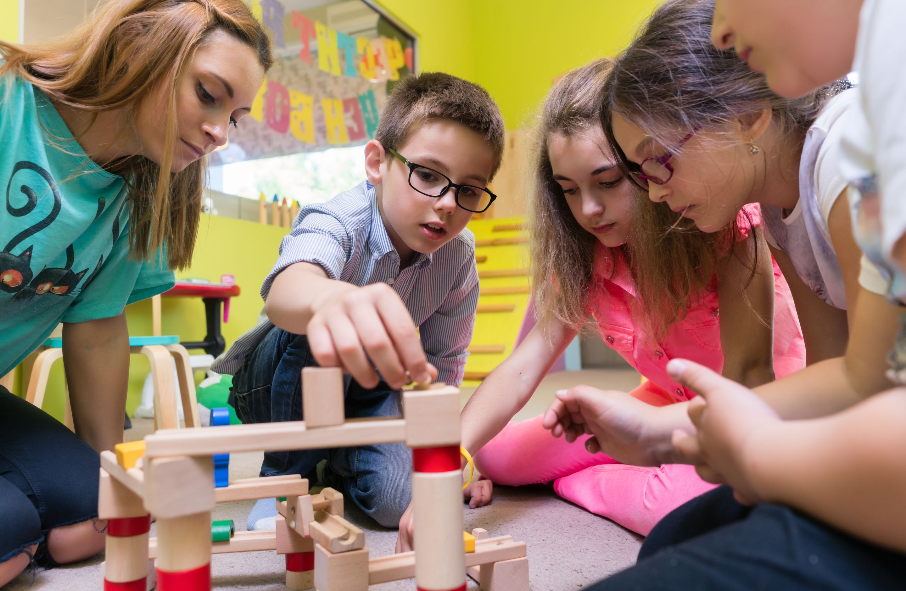 View of a teacher helping children with the construction of a wooden train circuit during supervised free playtime