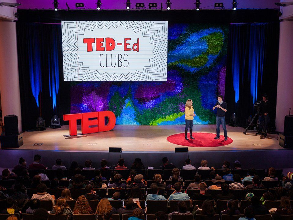 "A male and female adult are standing on a stage with a large audience in front of them. Standing on the stage are three big, red letters spelling, ""TED."" On a screen behind them says, ""Ted-ed clubs."""