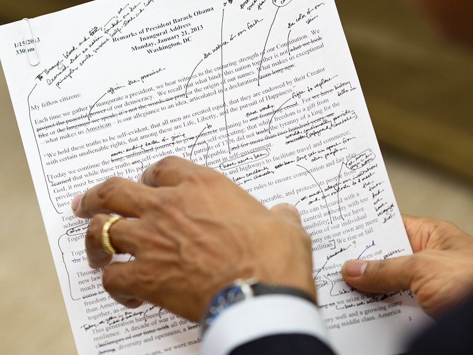 An employee of the Executive Office of the President of the United States is holding President Barack Obama's inaugural address. There are pen marks on it.