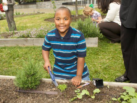 A young boy is kneeling on the grass beside a garden bed with a shovel in his hand, smiling at the camera.