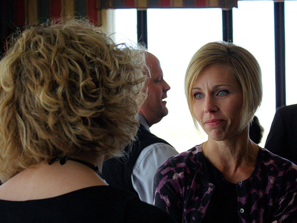 Two women are standing in a room, talking to each other. Other adults and standing and talking in the background.